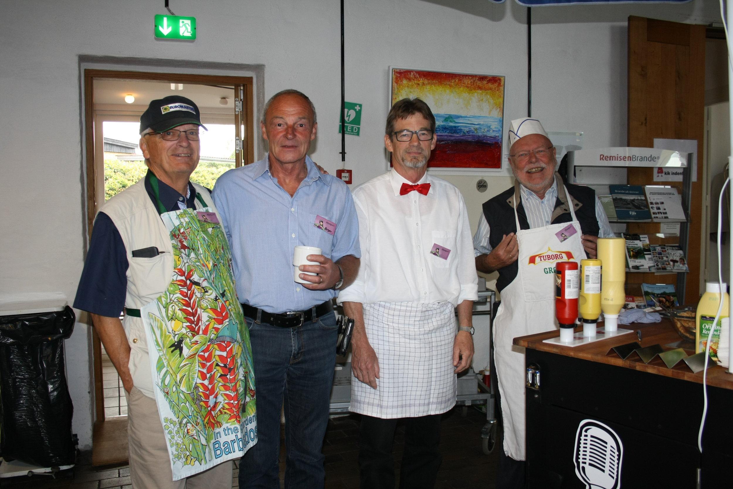 Her ses pølsemændene i 2014. I år bliver alle iført en flot rød propel, som Benny ses med her .   Fra venstre med hænderne dybt begravet i lommerne (heldigvis hans egne :)) Allan, derefter Birger som får sig en tår kaffe, Benny der er TOPKLAR i det rigtig outfit og til sidst Arne. Ud over HOTDOG denne dag er det selvfølgelig muligt at købe sandwich, kage, kaffe, the, vin og øl. Der er opsat borde hvor man både kan hygge, spise og strikke. Sæt dagen af, tag strikketøjet og veninderne under armen og kom og oplev en hyggelig dag!