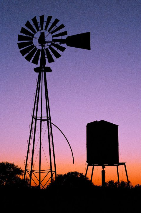 Sunset behind a windmill on the ranch