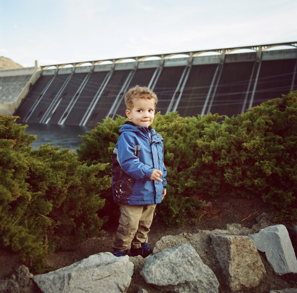 Coulee Dam, WA - November 11th, 2013: The Parker family enjoy the view of The Grand Coulee Dam from the park below the visitor's center. The Grand Coulee Dam began operating in 1942 and is one of the world's largest concrete structures.  Over a mile long when constructed it had a peak workforce of 7,700 and took a little over 9 years to complete.  In 1941 Woody Guthrie worked for the Bonneville Power Administration (the federal agency created to sell and distribute power from the river's federal hydroelectric facilities, in particular the Bonneville Dam and Grand Coulee Dam) for a single month, creating 26 or so songs called the Columbia River Ballads, including a song devoted to the dam called 