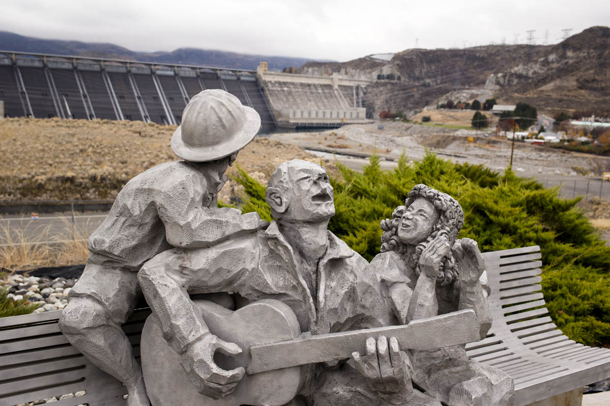 Coulee Dam, WA - November 10th, 2013: Across the street from The Grand Coulee Dam lies a statue titled After Work, made by Rich Beyer and Steve Love and dedicated in 1999 in honor of all those who worked at the dam.  Depending on who you ask the statue is either of Woody Guthrie or of a man singing a Guthrie song. In 1941 Woody Guthrie worked for the Bonneville Power Administration (the federal agency created to sell and distribute power from the river's federal hydroelectric facilities, in particular the Bonneville Dam and Grand Coulee Dam) for a single month, creating 26 or so songs called the Columbia River Ballads, including a song devoted to the dam called 