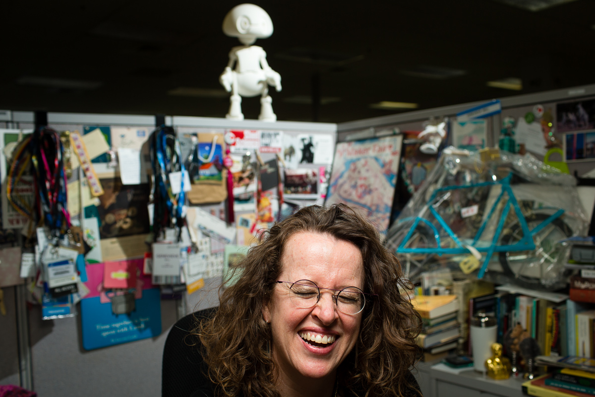 Hillsboro, OR - December 5, 2013: Genevieve Bell, a cultural anthropologist, poses for a portrait at her office in at Intel in Hillsboro, OR where Bell is the Director of User Experience Research, studying how consumers interact with new technologies. Behind her is Jimmy, a social 21st Century Robot, whose brains, design, and technical 3D printing are all open source. Credit: Leah Nash for the New York Times