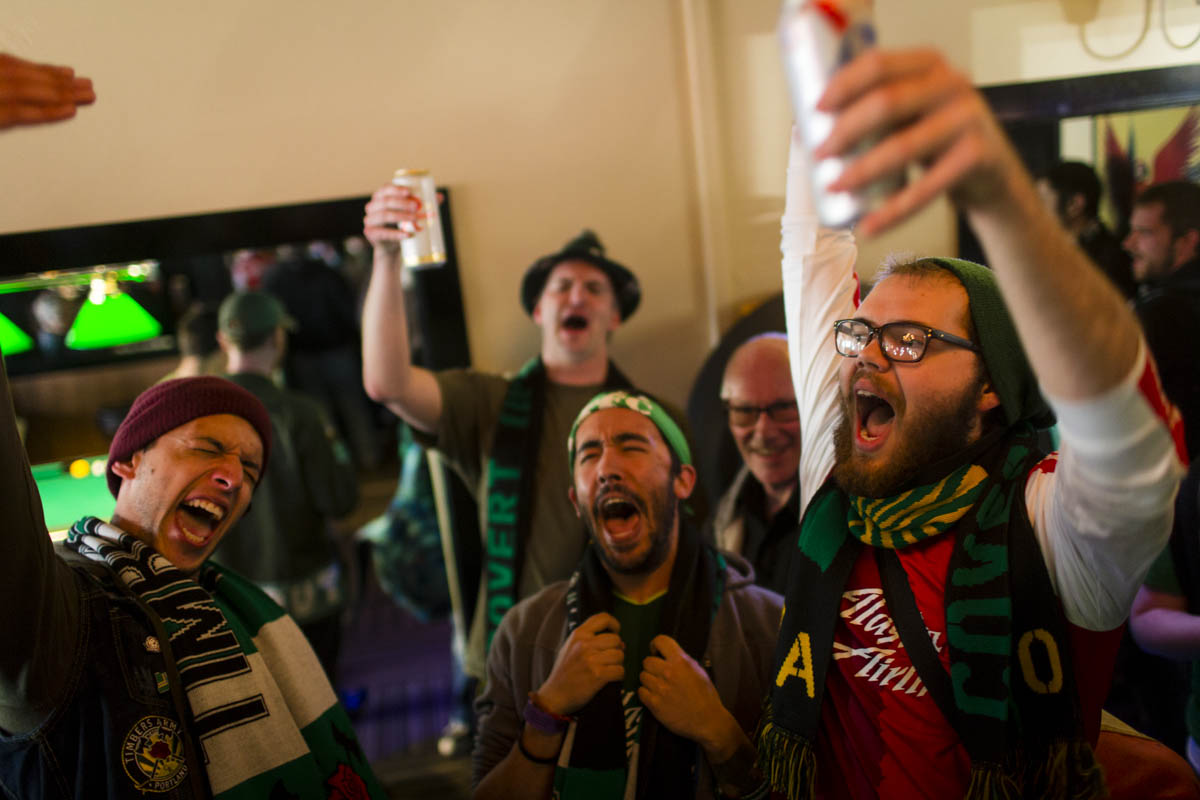PORTLAND, OR – October 13, 2013: Portland Timbers soccer fans partake in a few drinks and songs at Timber's fans bar, The Commodore, before a big game with rivals to the North, the Seattle Sounders. The Timbers are one of the three hottest franchises in MLS right now, all part of a soccer explosion in the Pacific Northwest, including the Seattle Sounders and the Vancouver Whitecaps.