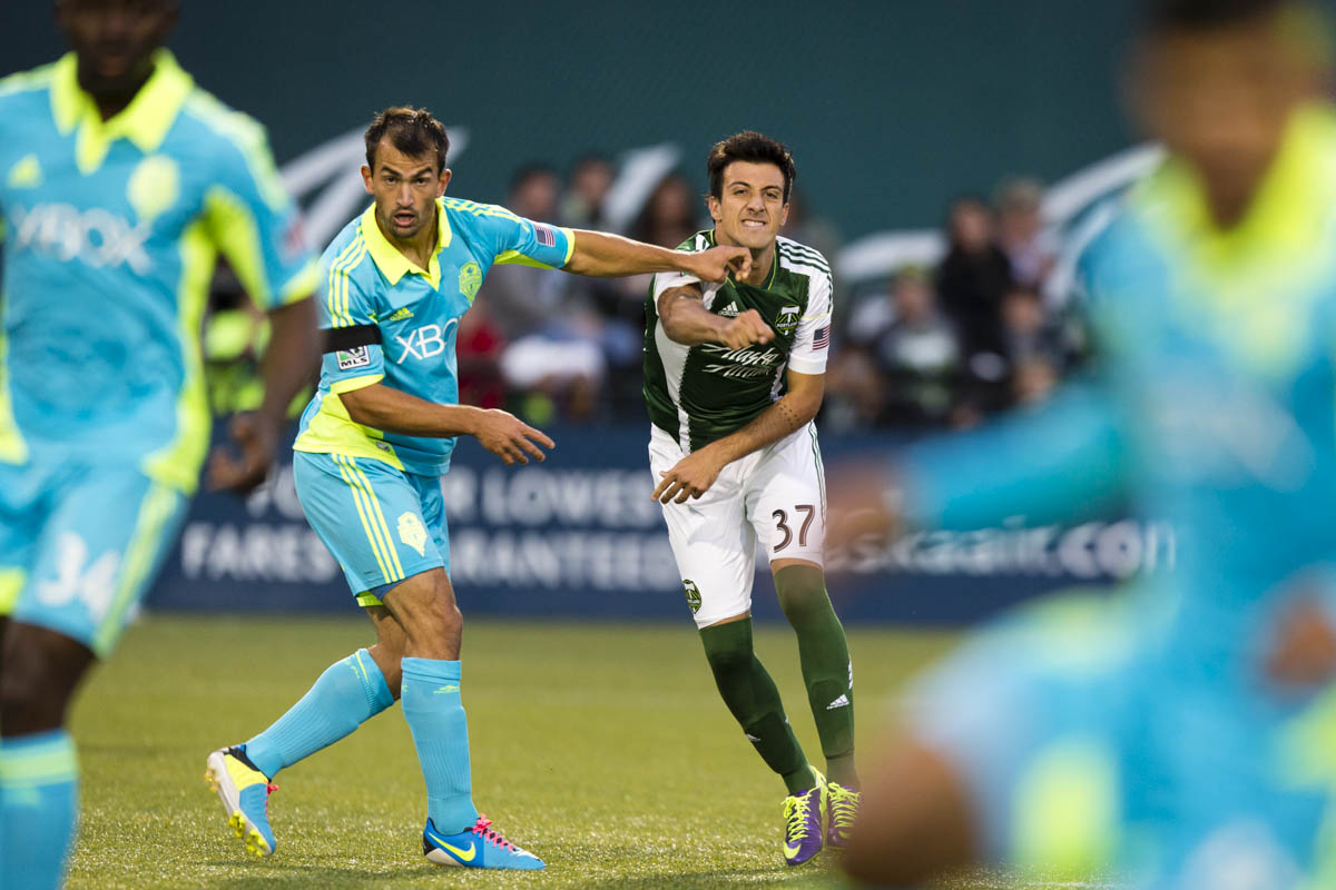 PORTLAND, OR – October 13, 2013: Portland Timbers' Maximiliano Urruti and Sounder defender Patrick Ianni battle for possession of the ball during the first half. The Timbers beat the Sounders 1-0 on their home field.  Credit: Christopher Onstott for the New York Times
