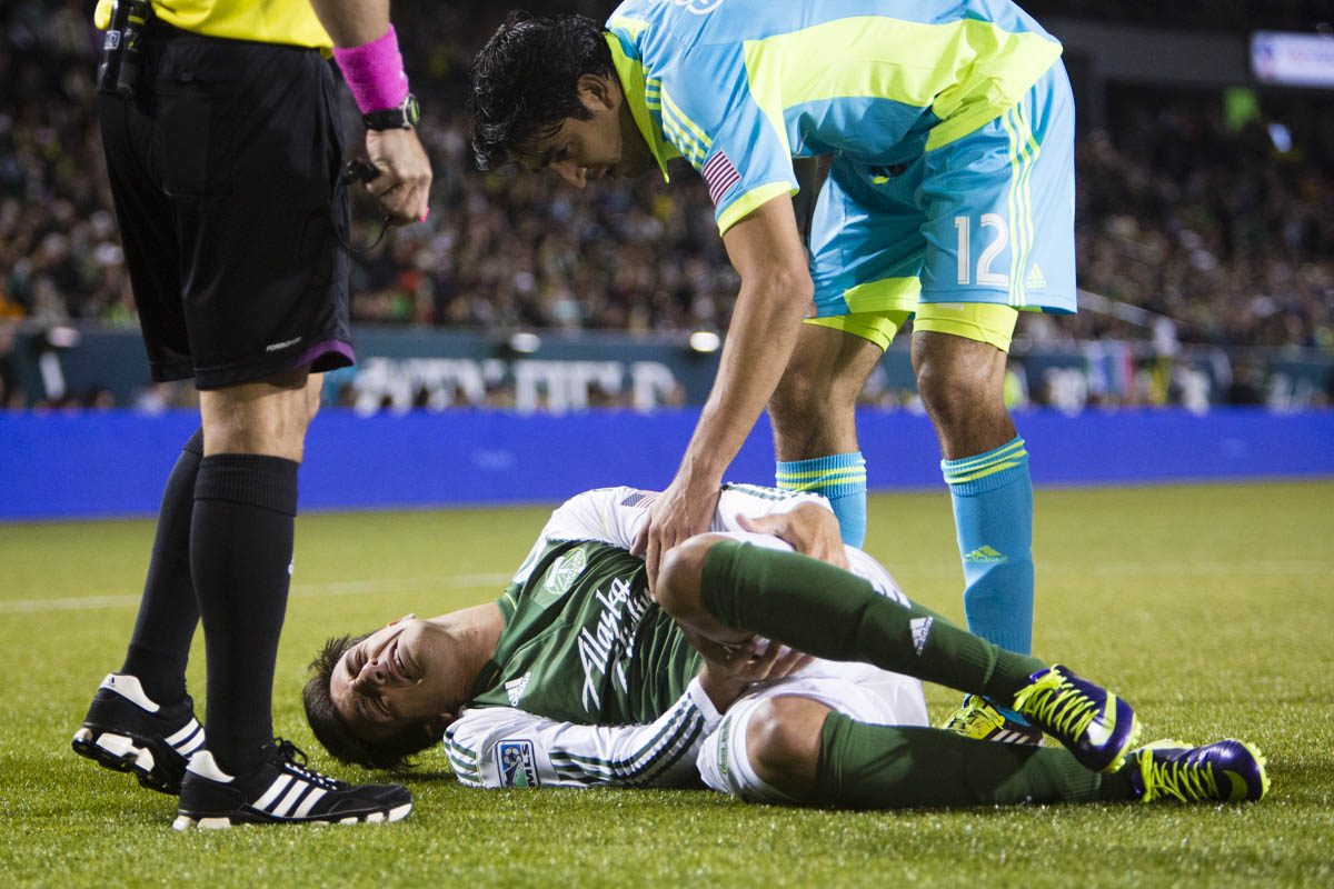 PORTLAND, OREGON - October 13, 2013 - Portland Timbers' Maximiliano Urruti holds his leg after going down injured, before being carried off on a stretcher at Jeld-Wen Field. The Timbers would go on to win the home rivalry match 1 to 0.  Credit: Leah Nash for the New York Times