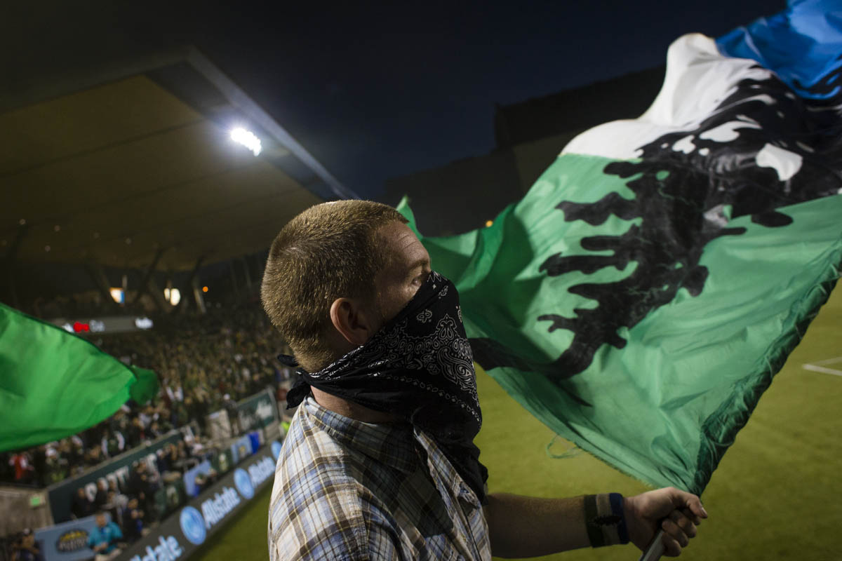PORTLAND, OR – October 13, 2013:  a Portland Timbers Army Capo waves a flag at the Jen-Weld Field after the Timbers score during the big game with their rivals to the North, the Seattle Sounders. The Timbers would go on to win the game 1 to 0. One of the three hottest franchises in MLS right now, the Timbes are part of a soccer explosion in the Pacific Northwest, including the Sounders and the Vancouver Whitecaps.