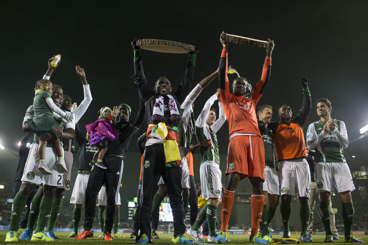 PORTLAND, OR – October 13, 2013: Portland Timbers' midfielder Kalif Alhassan (left) holds up a slice of wood representing his goal for the game, along side goal keeper Donavan Ricketts who shut out the Sounders, celebrate with their team after their 1-0 win over their rivals to the North, the Seattle Sounds at the Jen-Weld Field. Credit: Christopher Onstott for the New York Times