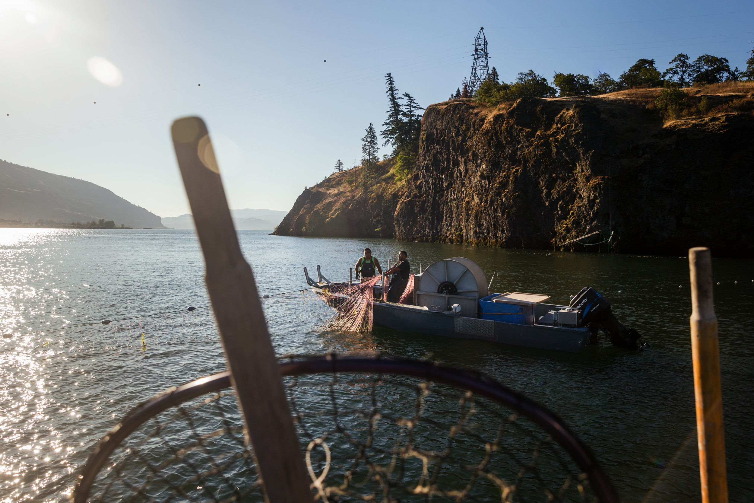 MOISER, OR – JULY 28th, 2016. Tribal Fishermen Sam George (black) and Howard Wahpat (green) use gill nets to commerical fish on the Columbia River near Mosier, OR. They were fishing on Friday June 3rd, the day that a Union Pacific oil train derailed outside of Mosier, OR and were some of the first on the scene. CREDIT: Leah Nash for The New York Times