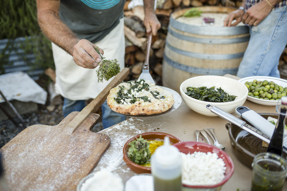 On November 7th, 2015 in Healdsburg, CA DaVero Farms & Winery Soilkeeper Michael Presley makes flatbread on a handmade brick oven for a get together held at the tasting room property of DaVero in Sonoma County. DaVero is a biodynamic family farm which produces small lots of Italian wine and olive oil in the Dry Creek Valley and is owned by Colleen McGlynn and her husband and QuickBooks creator Ridgely Evers. Sonoma has become America's test kitchen, 1768-square miles chocked full of wineries, dairies, micro-distilleries, bakeries, restaurants, gardens, and orchards.