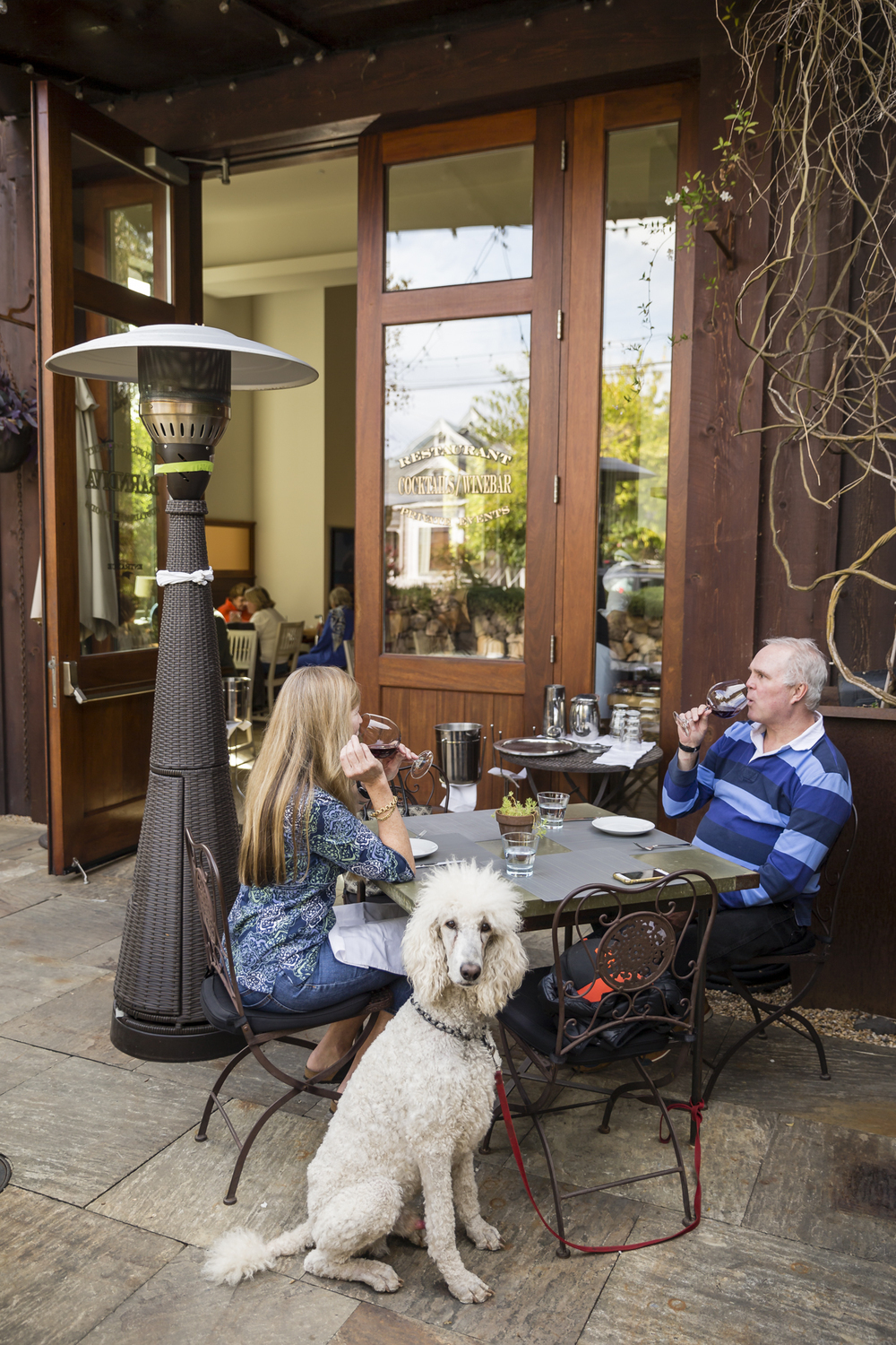 On November 5th, 2015 in Healdsburg, CA, Leslie French (lt) and Charles Hill (rt) and his poodle Coco dine at Barndiva, a farm-to-fork American eatery with an adjoining art studio and outside courtyard. Located in Sonoma, the 1768-square mile county is chocked full of wineries, dairies, micro-distilleries, bakeries, restaurants, gardens, and orchards and is quickly becoming know as the food-iest place on earth.