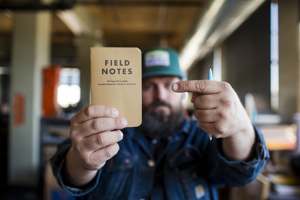"""PORTLAND, OR – June 14, 2015: Graphic designer Aaron Draplin poses at his favorite personal space, his office, in Portland, OR. Highlights include: 1. His collection of Flaming Lips posters  (pictured here top)2. His flat-file drawers full of vintage design (patches, stickers, metal name plates, old farm memo pads--there's a drawer for each)3. His circular """"Bicentennial"""" sign 4. His library of design books5. The portrait of him that one of his fans painted and gave to him6. His guitar and amplifier7. Some of the many products he sells including t-shirts, trucker hats, posters and Field Notes notebooks)."""