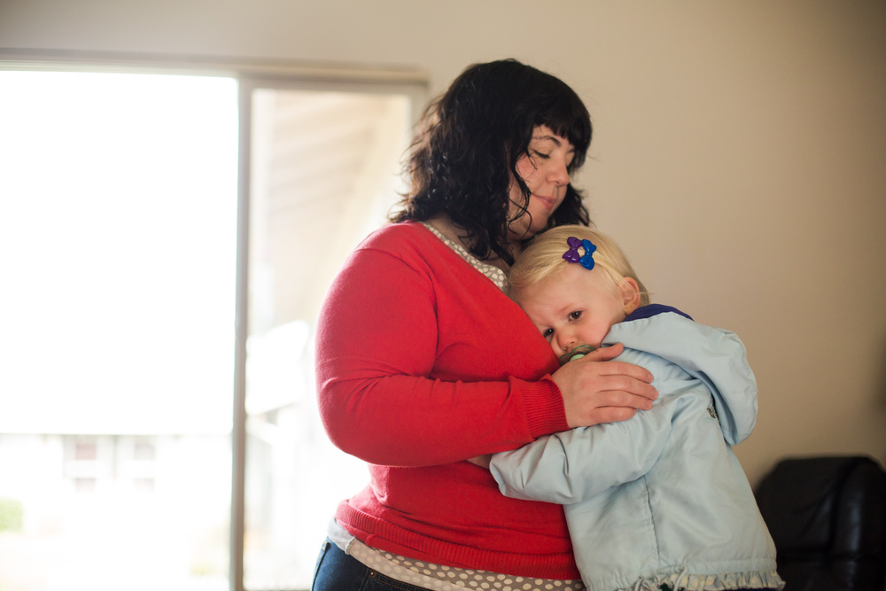 PORTLAND, OR - FEBRUARY 25, 2014: Jeanne Marie Johnson gets her two-year-old daughter Pearl Boehme ready for the day.  Johnson suffered from postpartum depression when her daughter was born and started seeing a therapist and was prescribed Zoloft to help with the syptoms. Doctors believe It is likely a combination of genetic risk factors, environmental stressors, financial strain, single motherhood, challenges raising the child, and hormones which cause it. CREDIT: Leah Nash for The New York Times