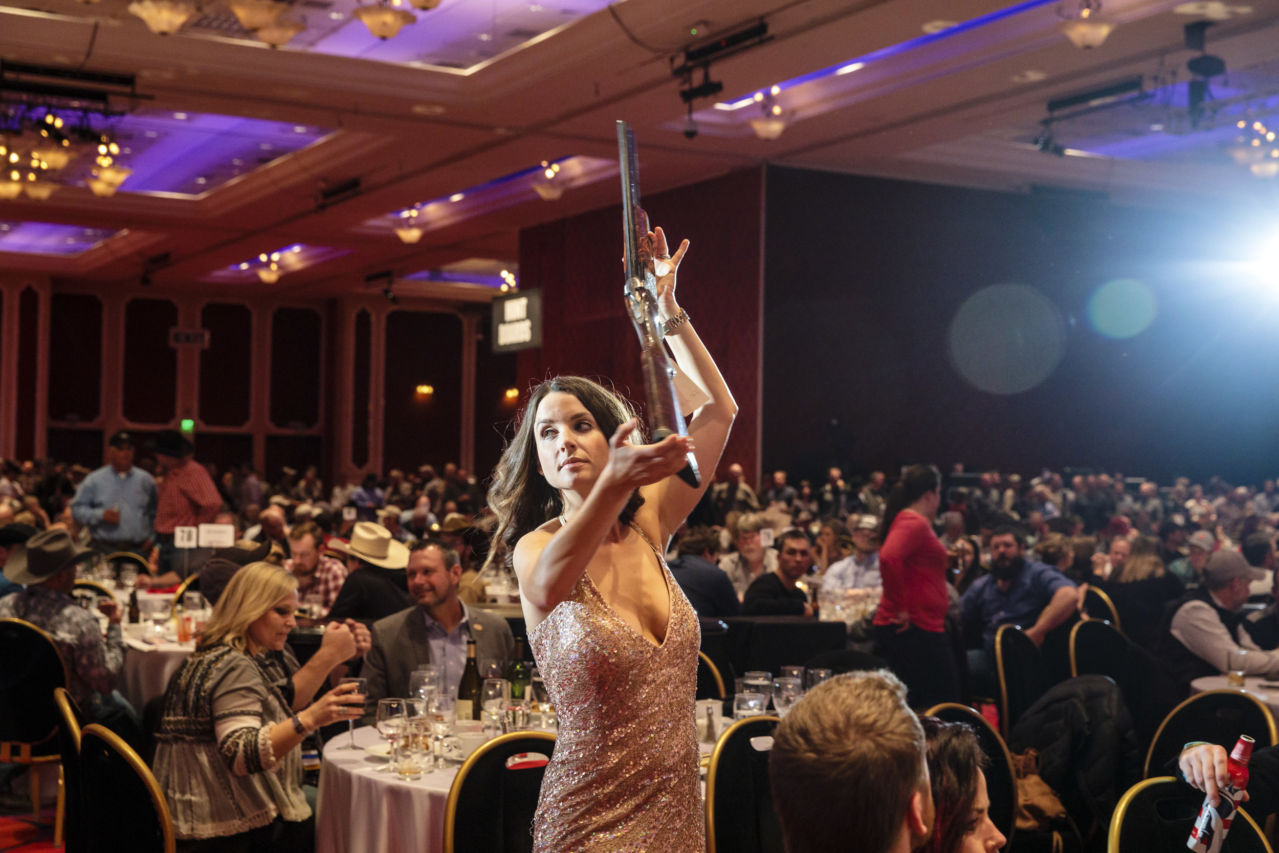 "RENO, NEVADA – JANUARY 20, 2017: Raffle girls display auction items at the Legacy Night banquet and auction that is part of the 2017 Wild Sheep Foundation Convention and Sporting Expo better known as ""The Sheep Show"", held at the Peppermill Resort, Spa & Casino in Reno , NV. The convention features more than 400 exhibits of guides and outfitters from around the world plus retailers selling gear, guns, art, taxidermy, jewelry, furs and every other outdoor item you can think of. The three-day event includes silent and live auctions, raffles, lectures, backpack races and more. Later that night, a bighorn sheep hunting license would be auctioned off for more than $300,000. Over the past 24 months, the Wild Sheep Foundation has directed more than $8.75 million to programs that include the promotion of wild sheep enhancement and conservation, habitat improvement, youth education, and sound wildlife management practices. CREDIT: Leah Nash for The New York Times"