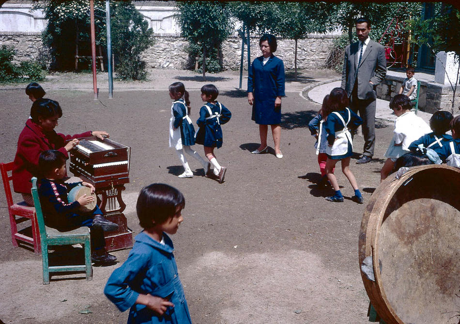 Young students dancing to music on a school playground.