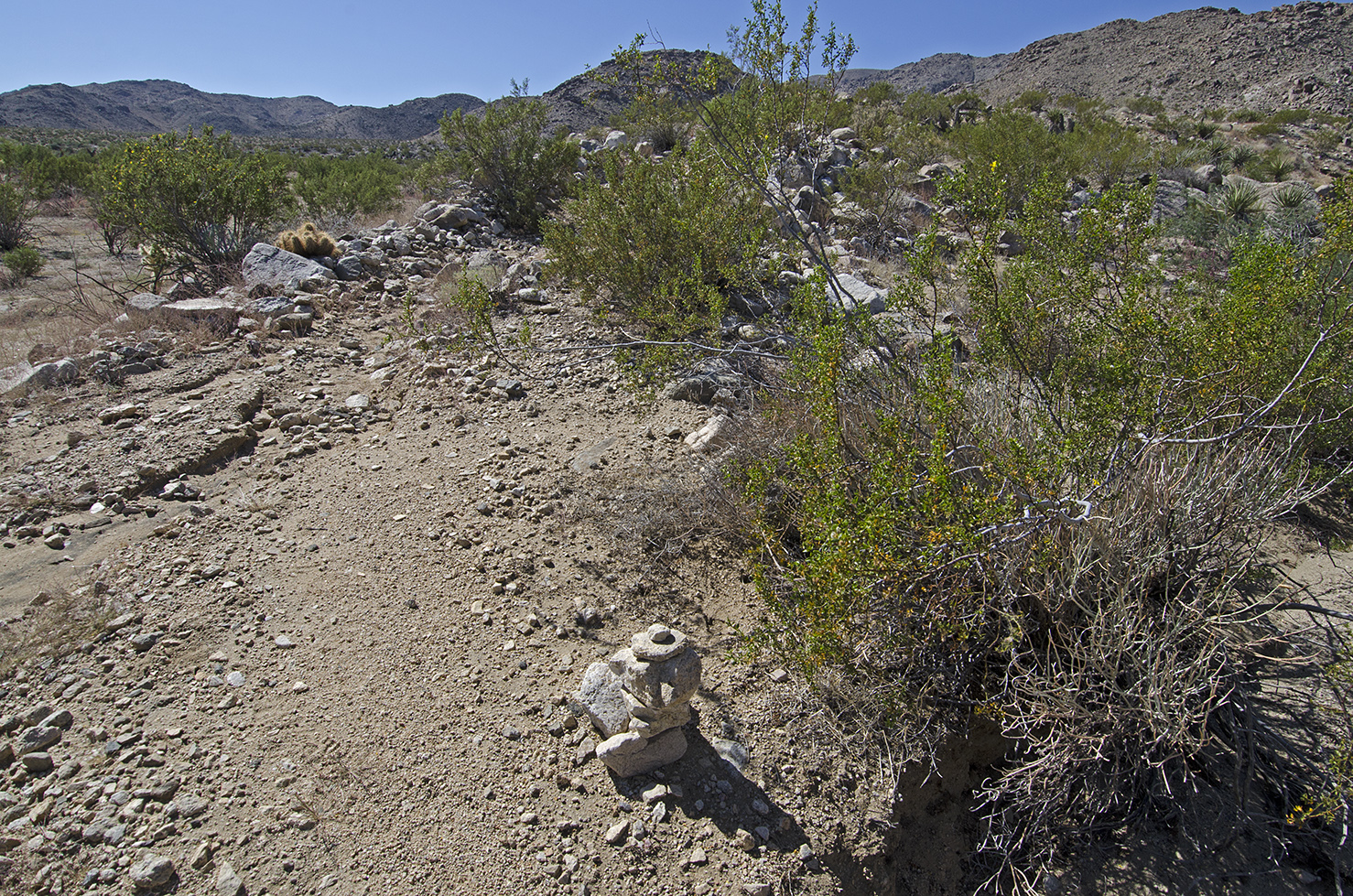 Another small rock pile marks the spot where the mining road begins to climb up the small ridge that will parallel the wash.