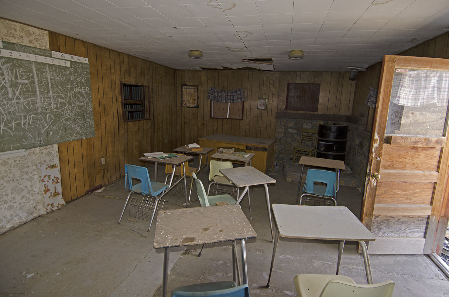 Inside the school house, a few student's desks, a chalkboard, a few pictures hanging on the wall and some bits and pieces of papers and books.