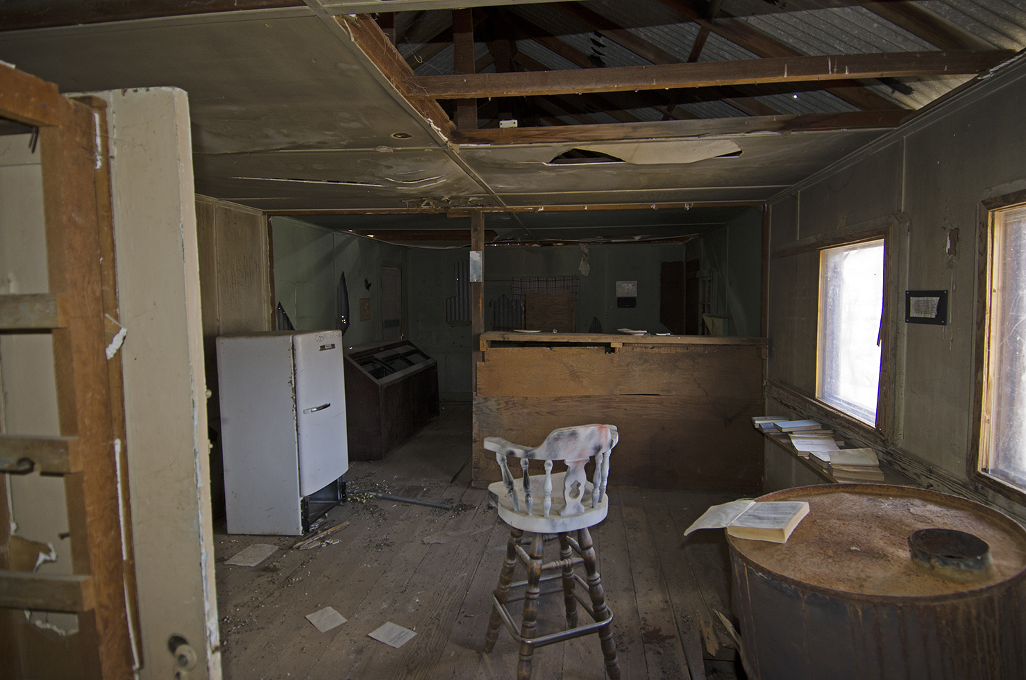 Inside the saloon. Note the old refridgerator and in the back what looks like an ice cream case. Another oil drum heater.