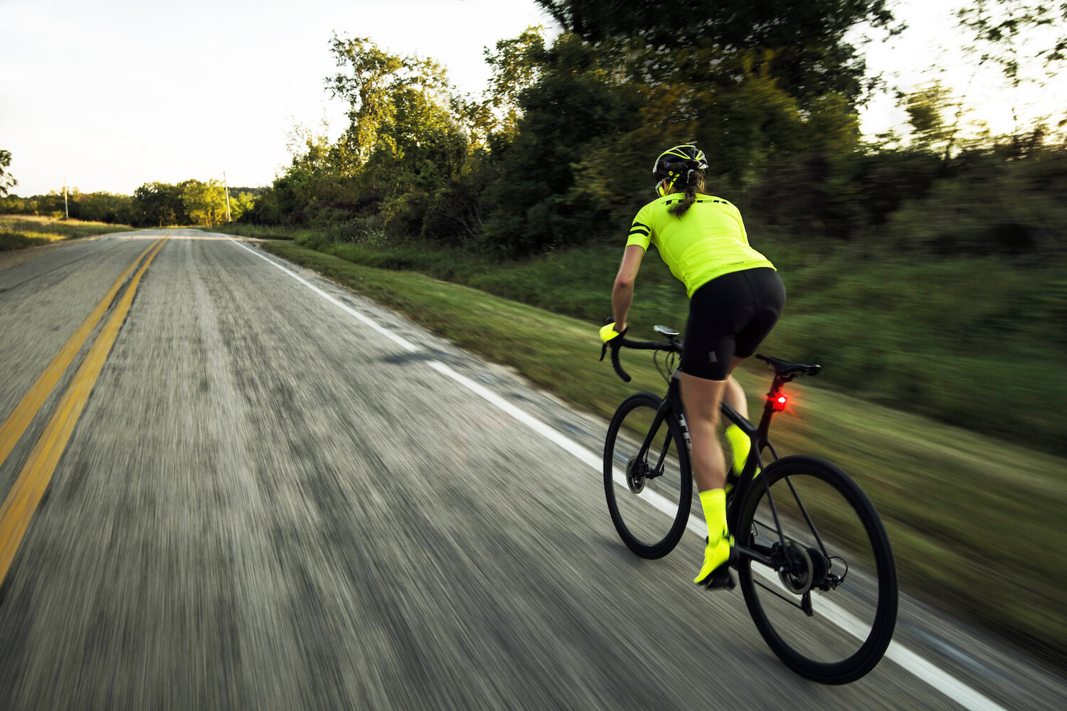 A bicyclist riding down a road, wearing bright colors.