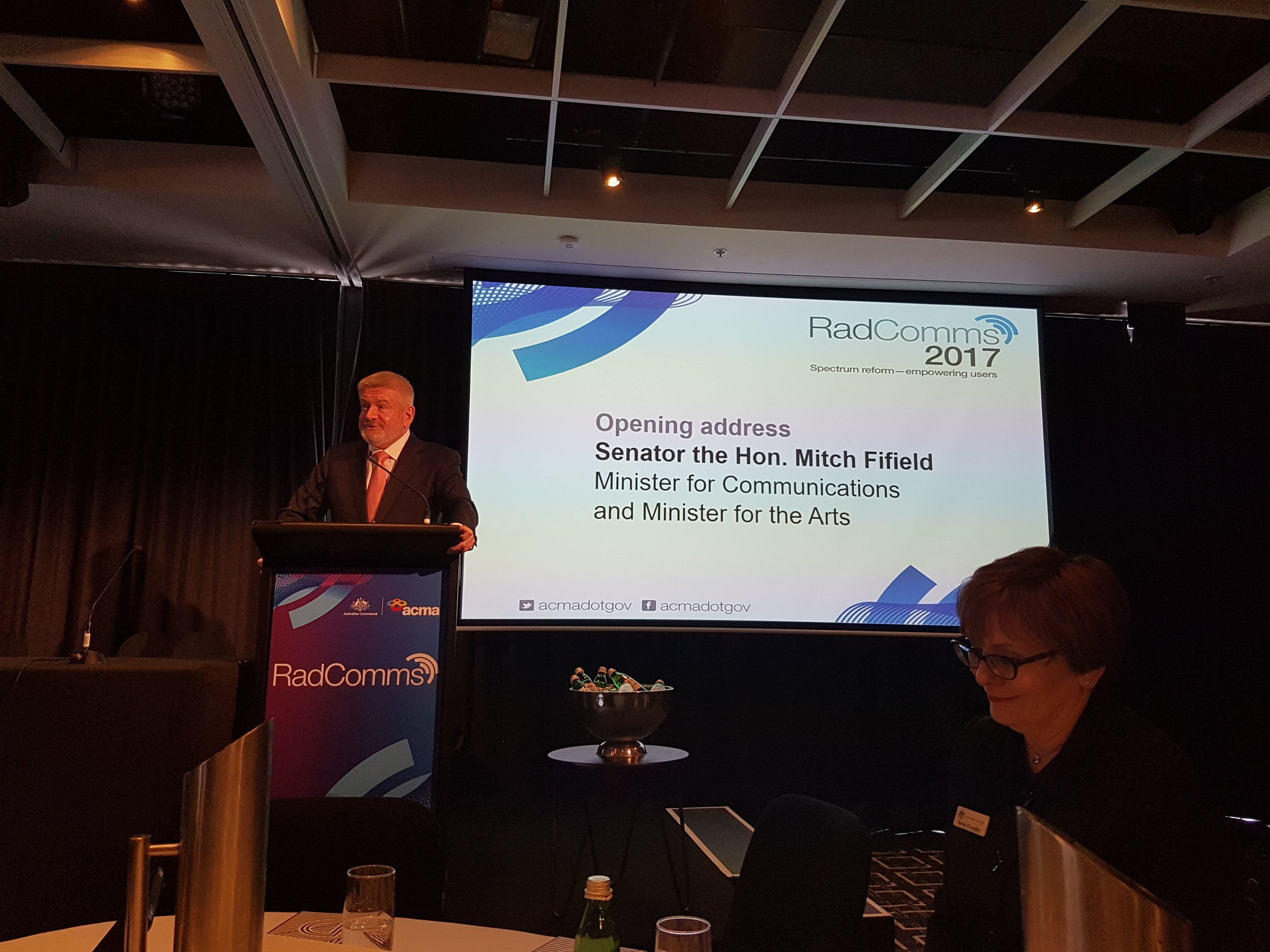 Honourable Minister Mitch Fifield, Minister for Communications and Minister for the Arts giving the opening address at RADCOMMS17. In foreground, the new Chairwoman of the Australian Communications Media Authority (ACMA), Derida O'Loughlin, the first female chairwoman of the ACMA.