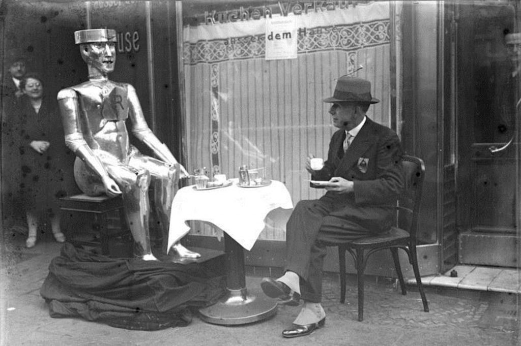 "Berlin (March 1930). Original caption: The first artificial machine man in Berlin! ""Robot"", the first artificial machine man, was invented by his inventor, the English engineer, Captain W.H. Richards presented for the first time to the public in the conservatory in Berlin. The artificial machine man ""Robot"" can speak, turn his head, hold objects and bow. He is made entirely of steel. ""Robot,"" the artificial machine man ""has breakfast"" in the streets of Berlin with his inventor, the English engineer Captain W.H. Richards."