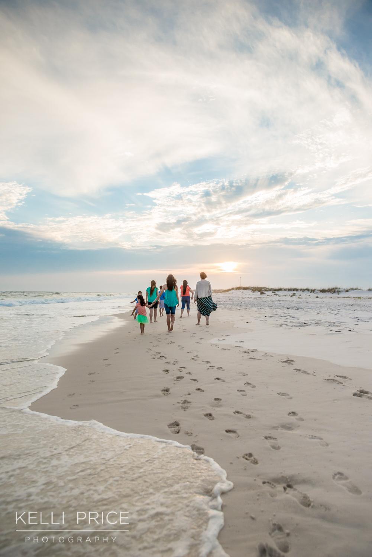 Family walking into the sunset on Destin Beach
