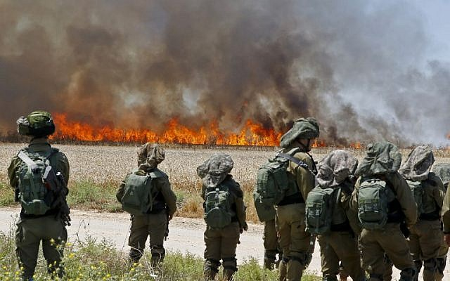 Israeli soldiers walk amidst smoke from a fire in a wheat field near the Kibbutz of Hahol Oz, along the border with the Gaza Strip, which was caused by incendiaries tied to kites flown by Palestinian protesters from across the border (May 14, 2018 - Jack Guez/AFP)