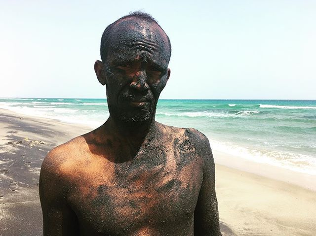 A Somali soldier named Ayanle scrubs his skin with black sand from the Gulf of Aden.