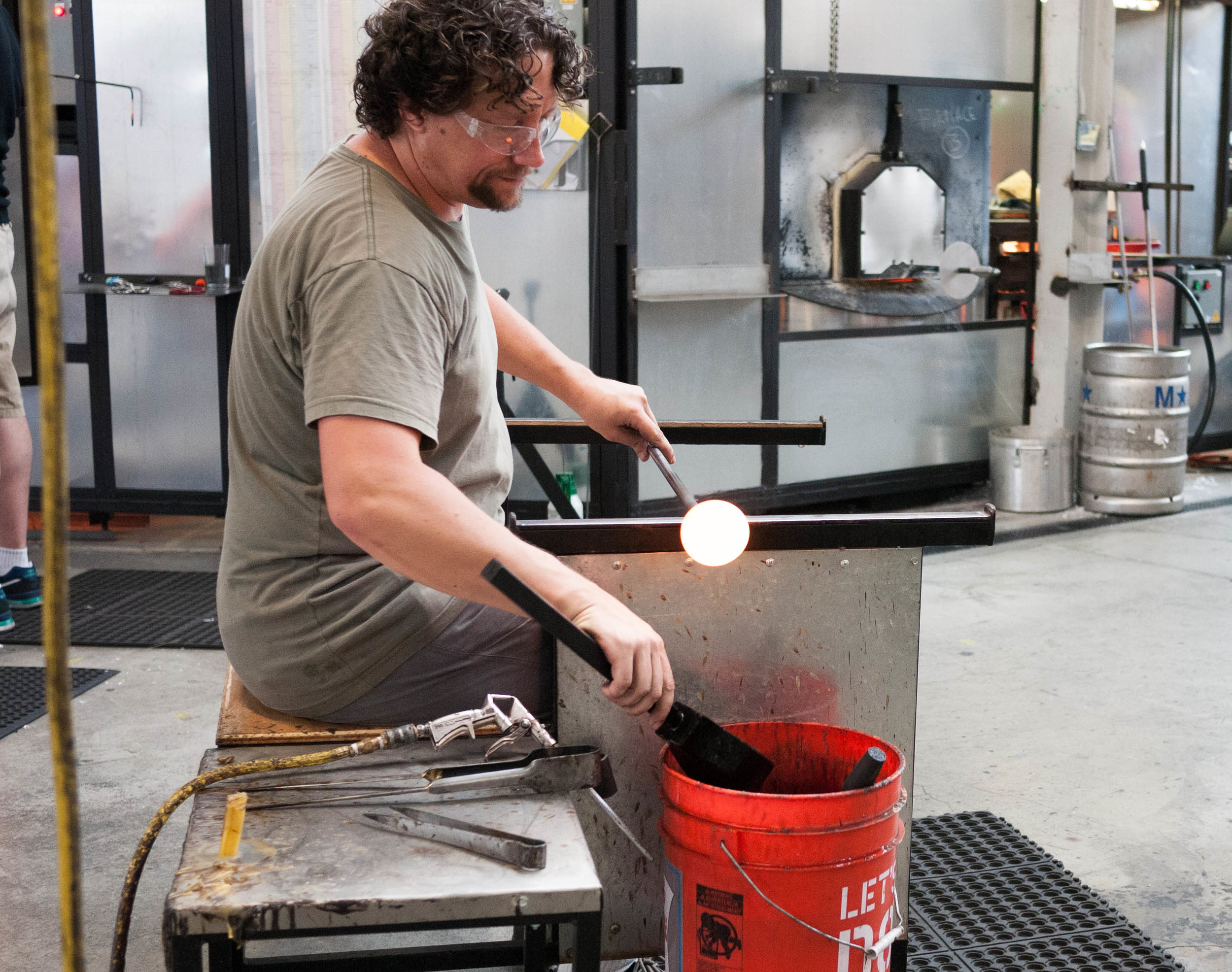 Step 2 in the process is to shape the glassybaby into its classic round shape. This glassworker is using an iron cup and water to shape and cool the votive.