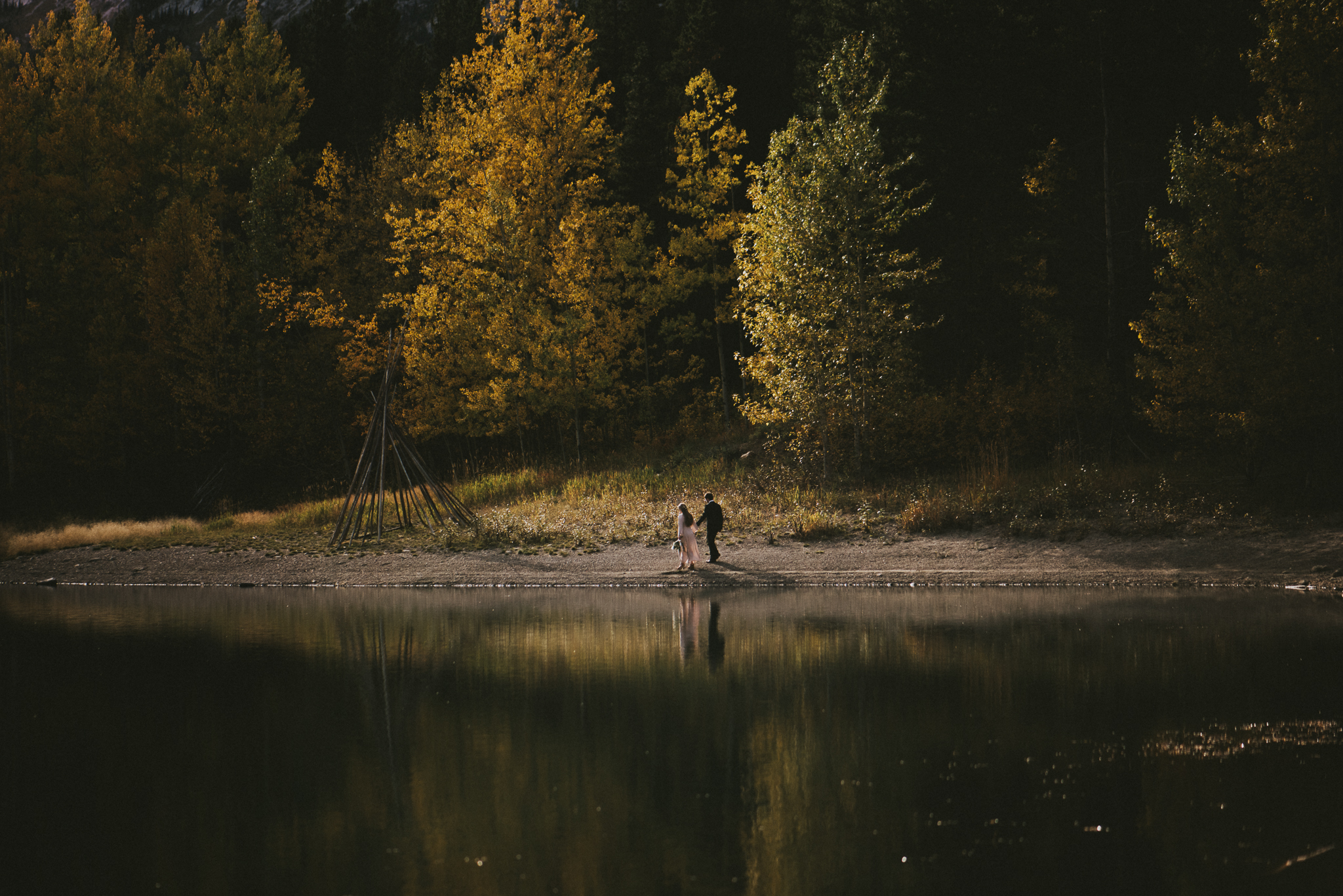 bride groom by water reflection forest elopement kananaskis