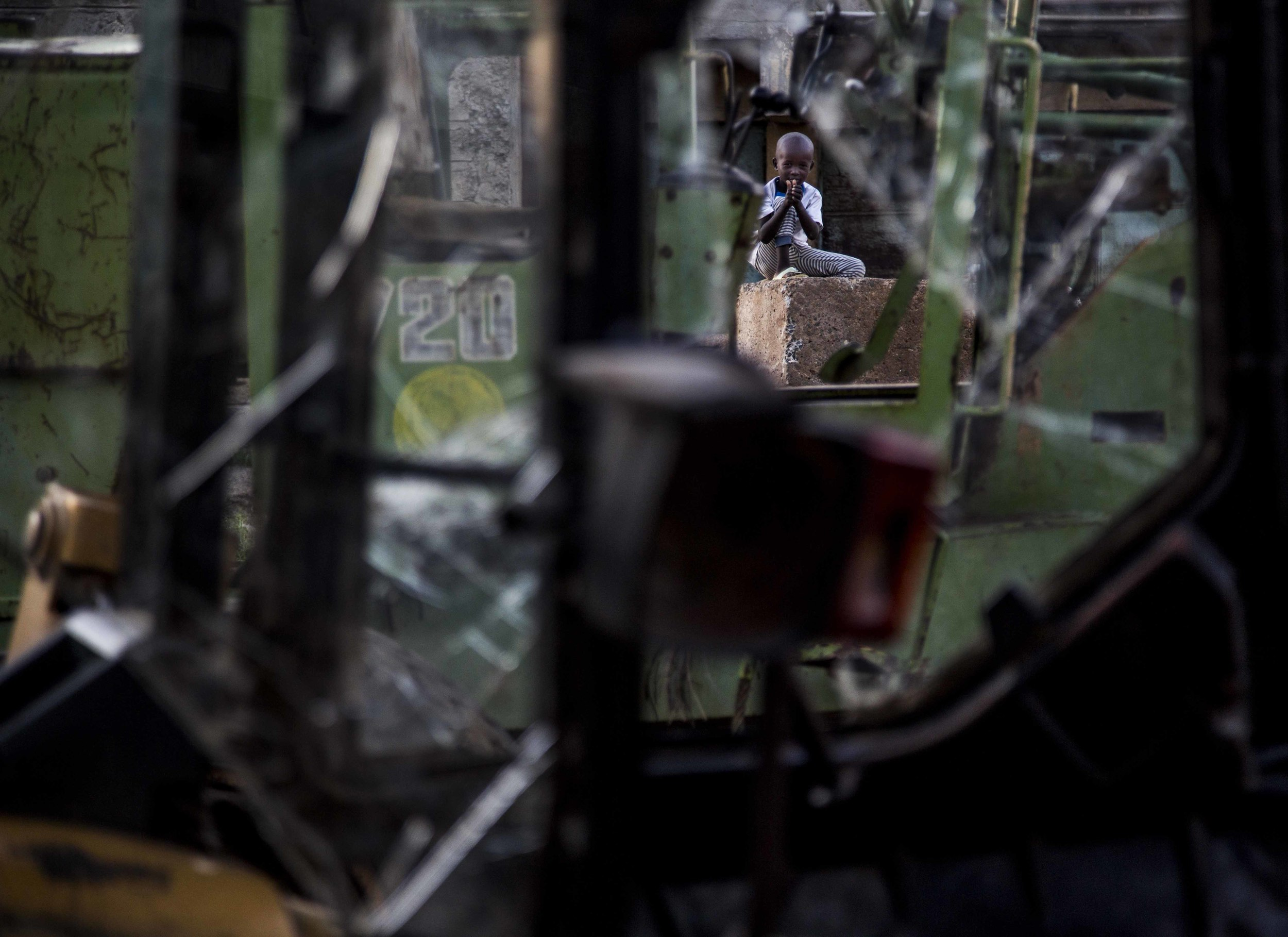 A child plays near broken down heavy machinery adjacent the Dandora Dumpsite.