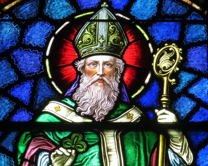 A stained glass recreation of St. Patrick holding a shamrock, found in Junction City, Ohio. Photo by Nheyob/Wikimedia Commons.