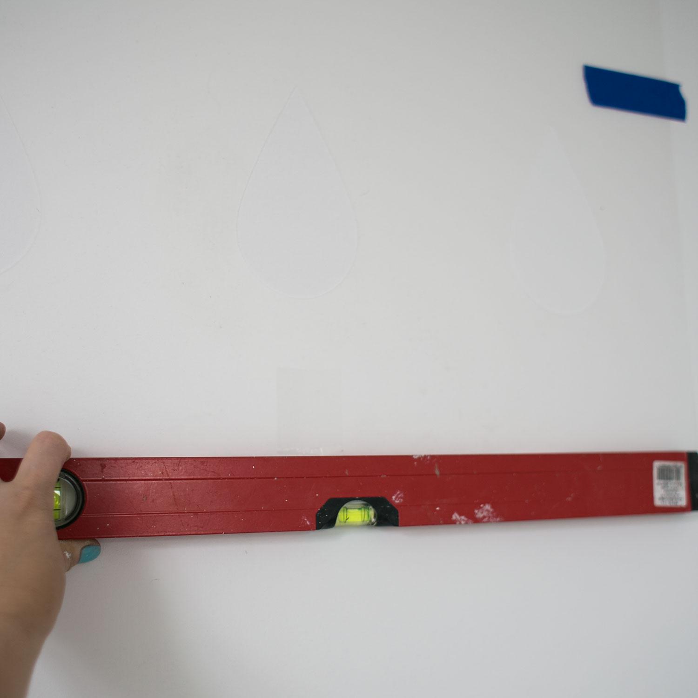 """- 3 -  wybieramy miejsce na ścianie, z którego zaczynamy malować, przyklejamy szablon do ściany na dwie górne taśmy """"tak na oko"""" i dopiero potem sprawdzamy poziom poziomicą. regulujemy, jeśli jest krzywo, odklejając i przyklejając górne taśmy."""