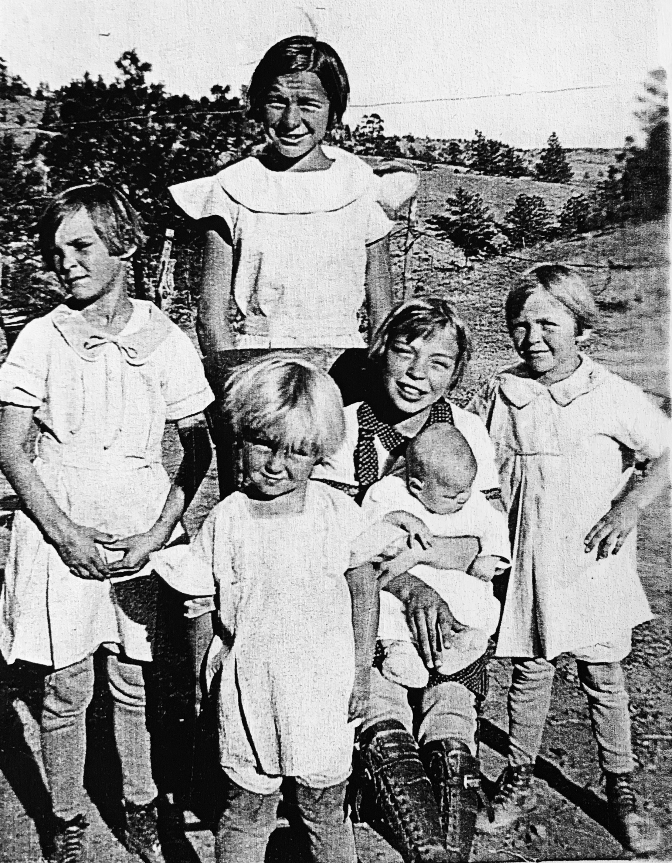 My mom is the baby being held by one of her siblings. My Aunt Mary is the little blonde with the sun in her eyes, standing front and center of everyone.