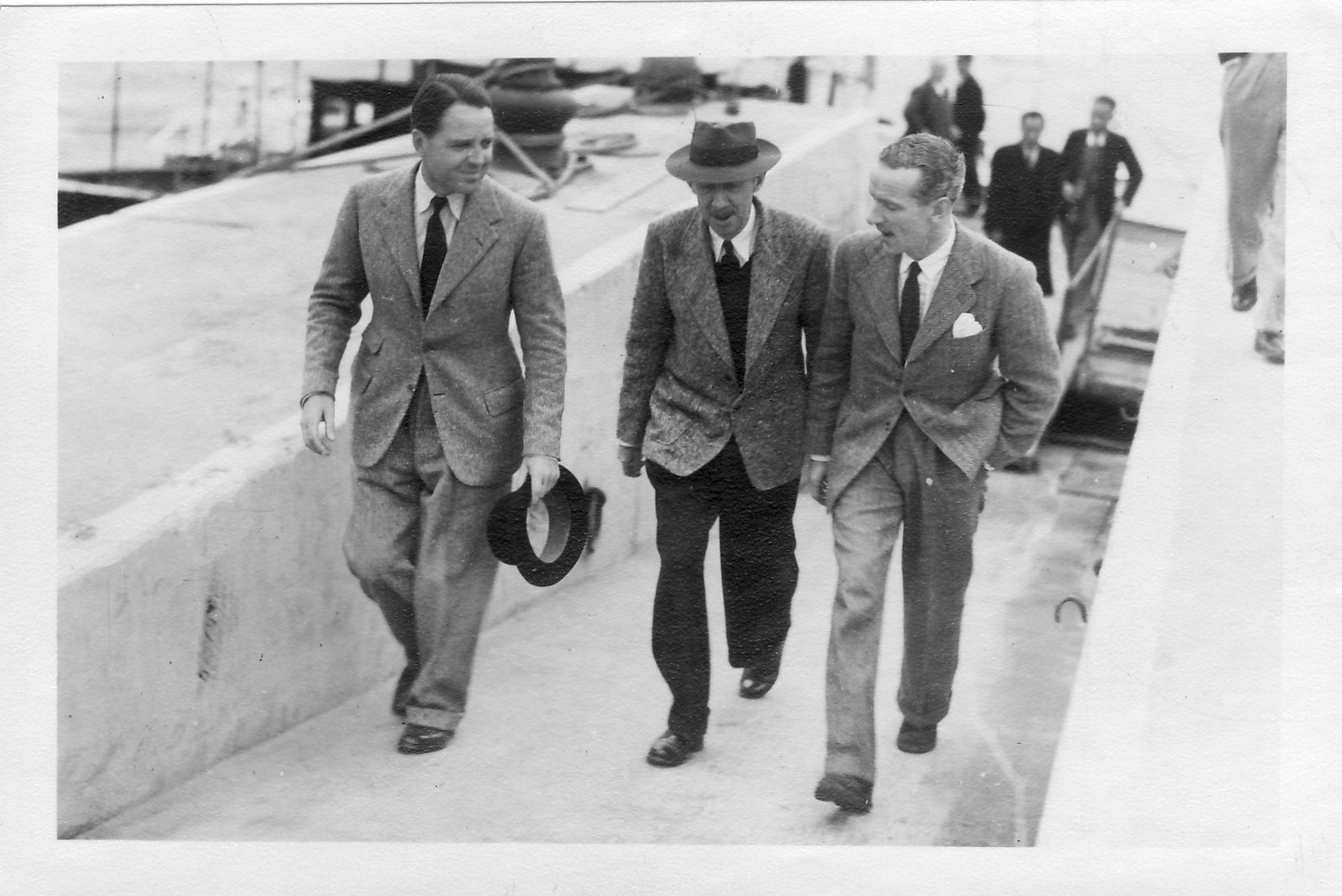 Colonial Secretary MacDougall (right) returns from a trip, greeted by Max and DCA Albert Moss, January 1947