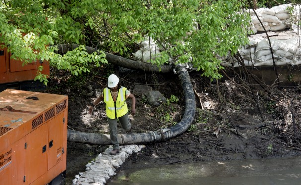 A worker monitors cleanup efforts after a sewage spill on the Capital Crescent Trail in Washington on May 1. (Bonnie Jo Mount/The Washington Post)
