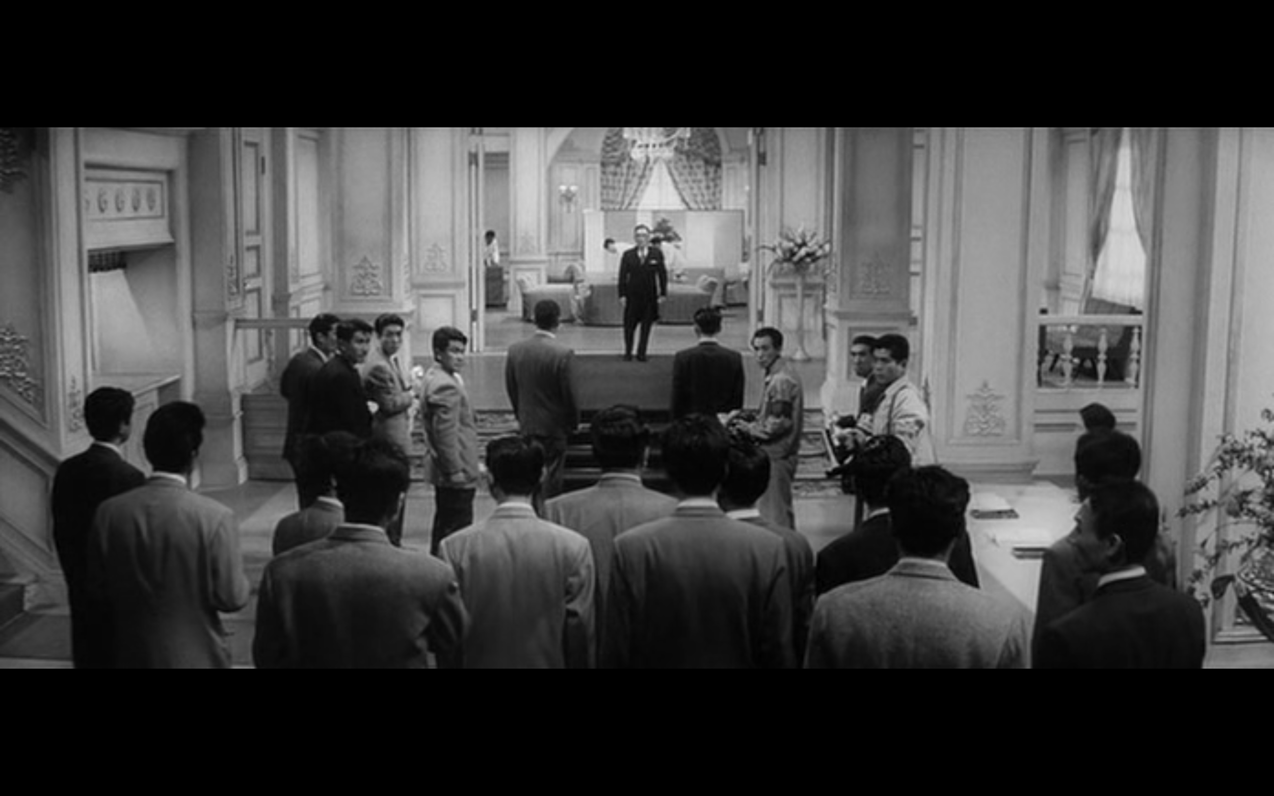 Do you see it? Kurosawa uses clear staging and clean composition to build shapes within his shots. Wada, the character at the top of the frame, serves as a point for two triangular layouts in this shot. From  The Bad Sleep Well  (1960), Dir. Akira Kurosawa.