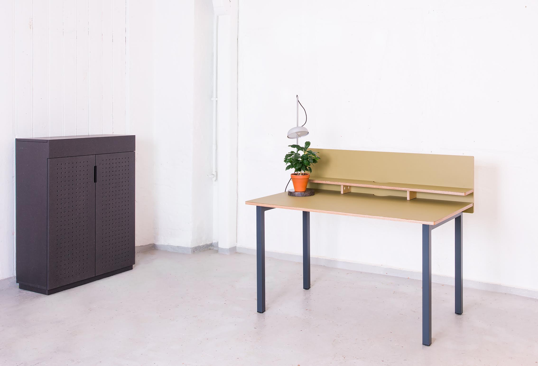 On the picture is a custom cabinet in solid anthracite Valchromat - with perforated fronts for sound absorption, designed by Norwegian interior architect Ellen Ledsten - along with Hallgeir Homstvedt's UT desk and the KI light.