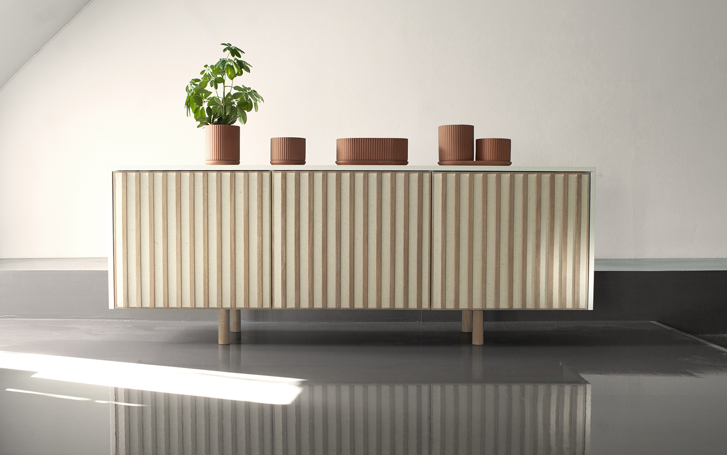 Klorofyll table pots in Terracotta - designed by Anderssen & Voll + dB Silent sideboard by Jonas Stokke and Øystein Austad of StokkeAustad, featuring thick acoustic wool felt in the held in place by solid oak wood slats.