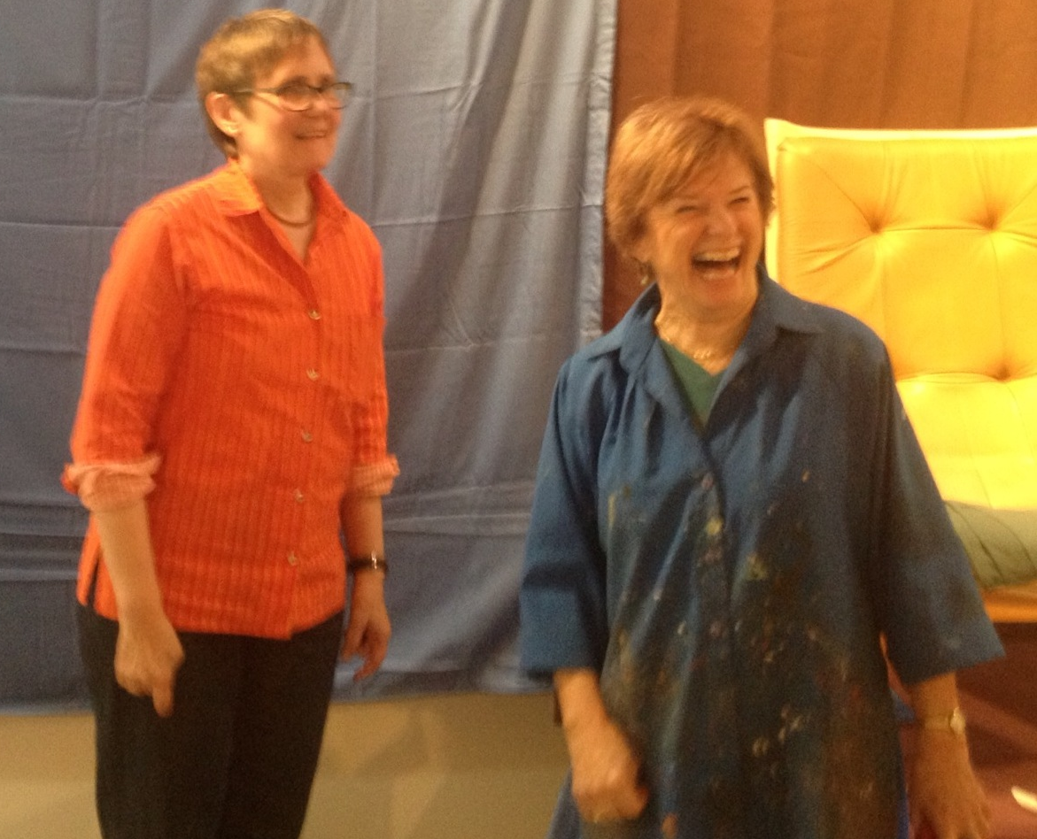 Catherine Kehoe and Sally Hamilton share a laugh in Marcia Burtt's gallery, transformed into a figure painting studio.