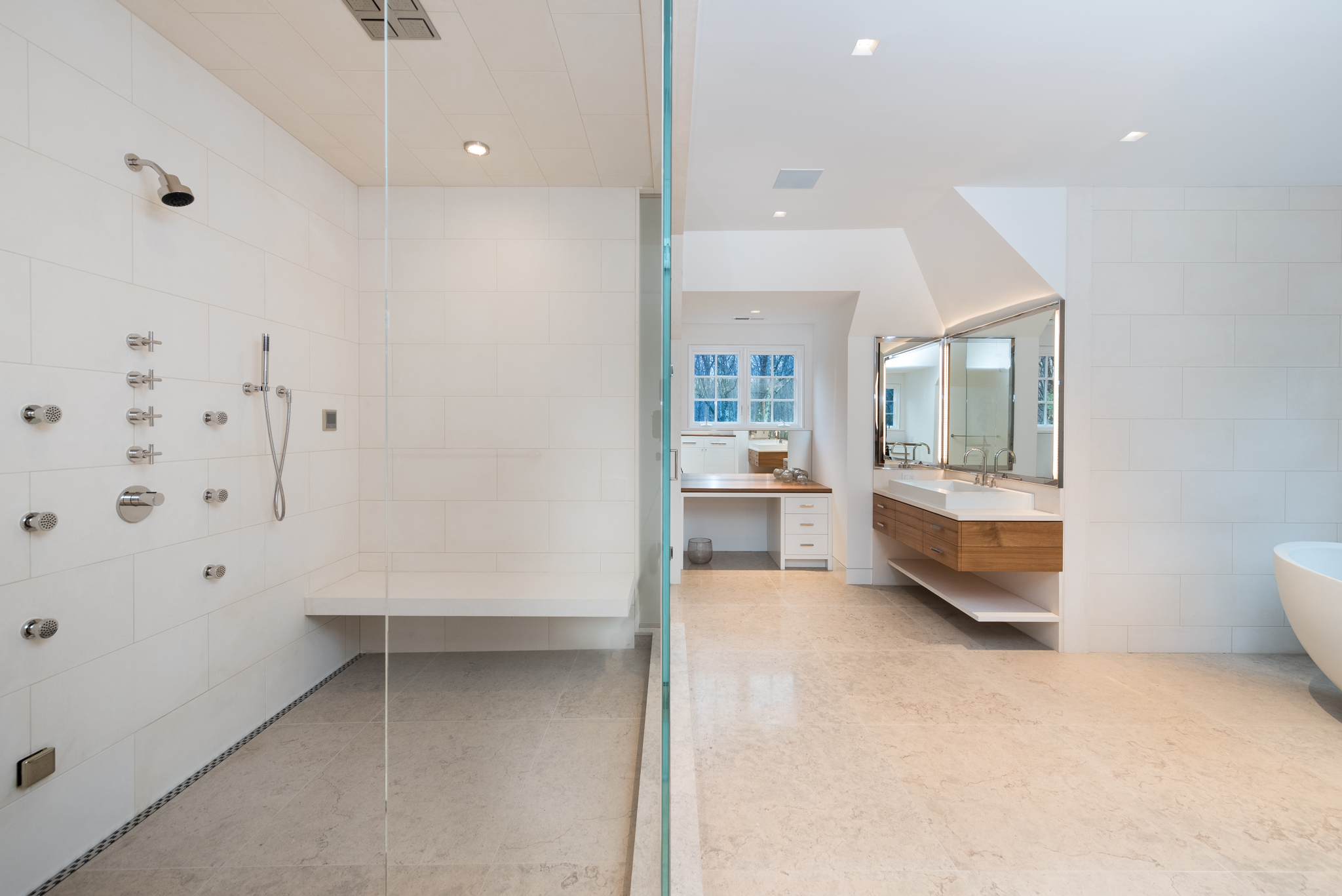 OVERALL:  The shower includes a ceiling mounted rain head, a wall mounted shower head, a handheld shower and 6 body sprays - all of which can be turned on simultaneously without any water pressure reduction.  The floating limestone bench allows a place to sit in the steam shower.