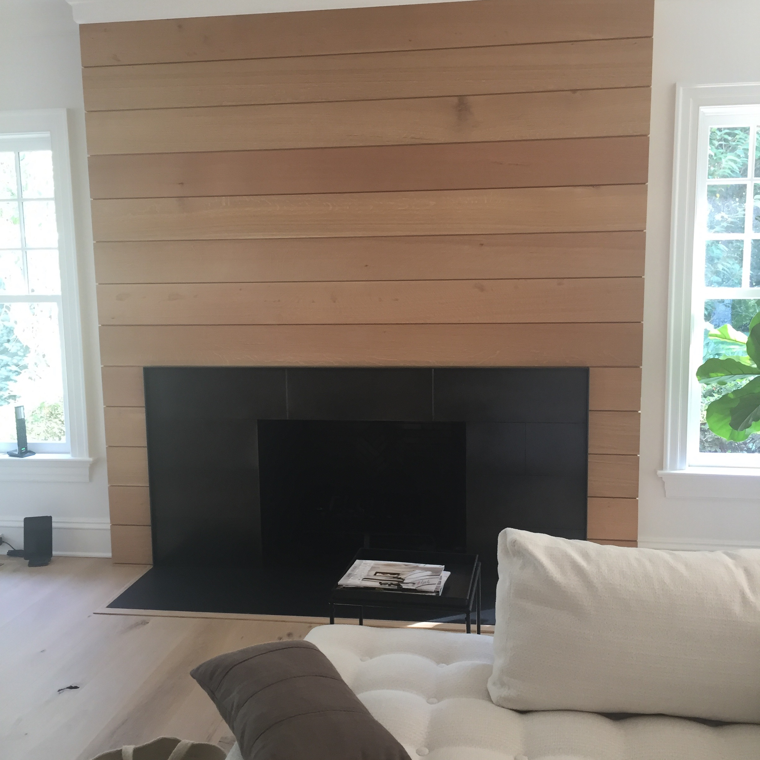 FAMILY ROOM FIREPLACE:  An out-of-scale large traditional wood mantle and stone surround were demolished and replaced with a clean, white-oak ship lap wall treatment and a blackened steel surround.