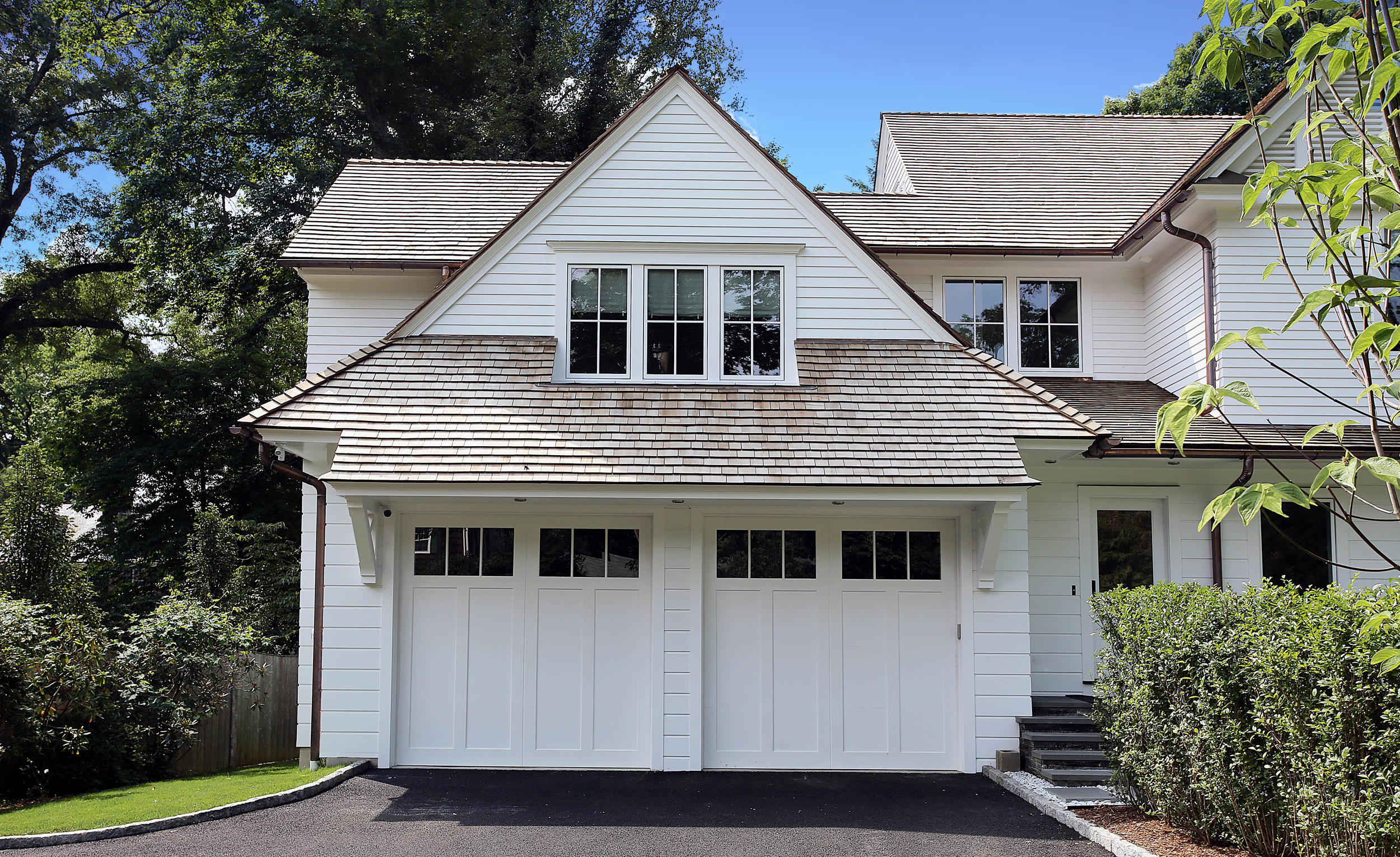 On the Garage portion of the front elevation, the louver panels were not used in the gable end and the entire roof form is dropped from the height of the other two gables.  This was done to de-emphasize this form - making the main block of the house the focal point from the street and visually reduces the overall bulk of the house along the streetscape.