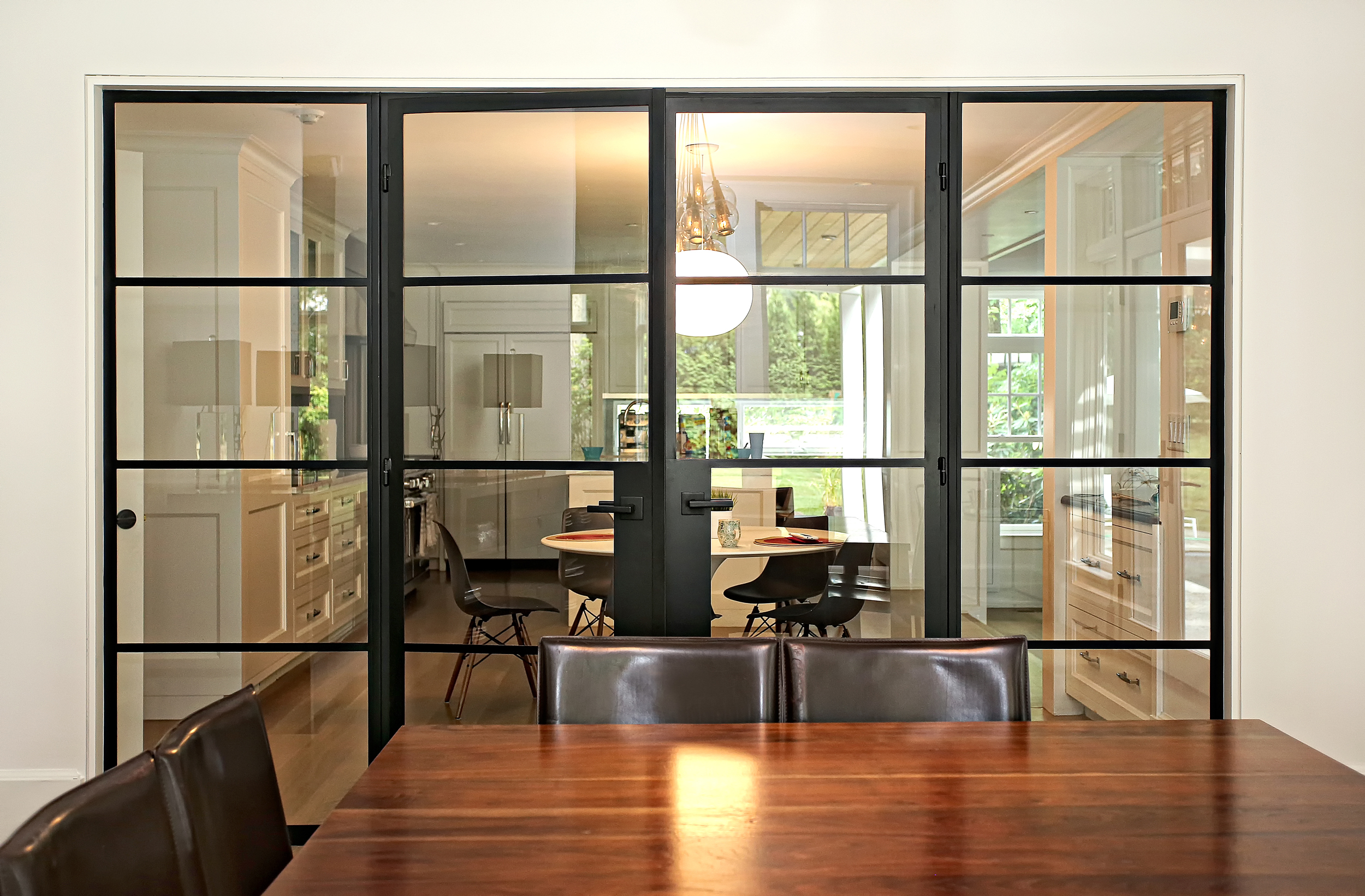 This is the view from the Dining Room into the Kitchen area.  We designed these steel doors to seperate the space, but allow a view from the Kitchen out to the yard through the Dining Room.
