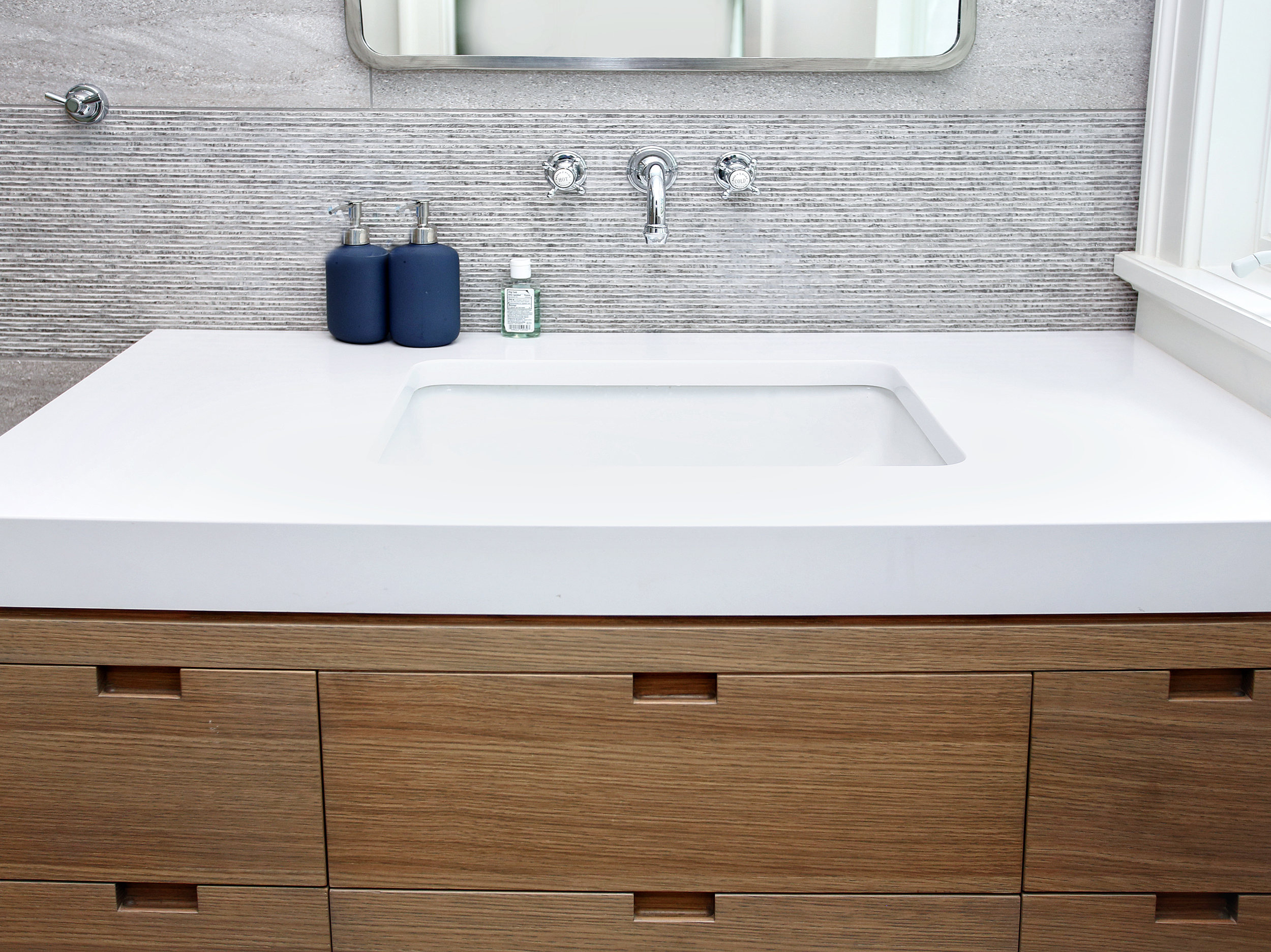 "In the boys bathroom, large shower and wall behind the vanity were clad in a porcelain tile that resembles concrete.  We used alternating bands of two textures along the full height of the walls.  The vanity is a custom white oak cabinet with built-in finger pulls.  The counter is a mitered white quartz counter so that the edges appear 3"" thick.  The countertop material and cabinet are seperated by a 3/8"" reveal to give a shaddow and finished look to the flush condition."