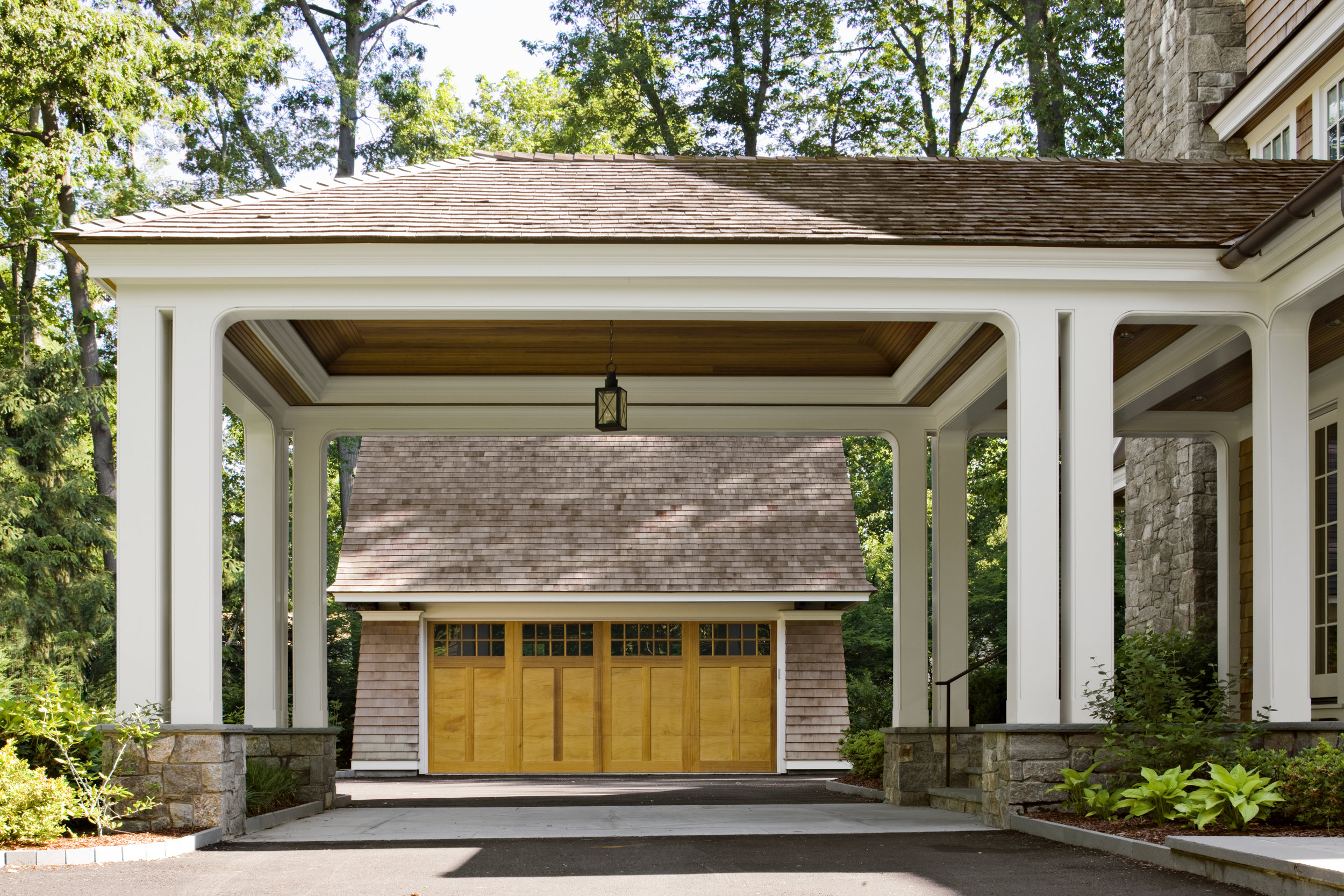The Porte Cochere serves as a place to park the car to unload kids, dogs and groceries.  It also allows for a detached garage in the rear yard which reduces the visible mass of the front elevation, and de-emphasizes views of garage doors from the street.  The paving at the porte cohere changes from blacktop to bluestone to break up the driveway and emphasize the side entrance into the mudroom.  The driveway edge is a vertically installed bluestone instead of the typical belgium block.