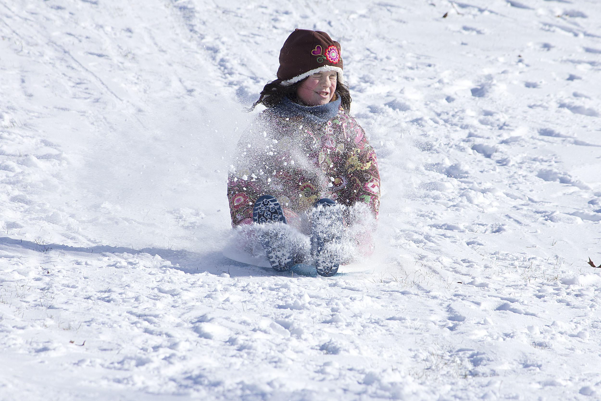 Norah, 7, sleds downhill as snow kicks up in her face.