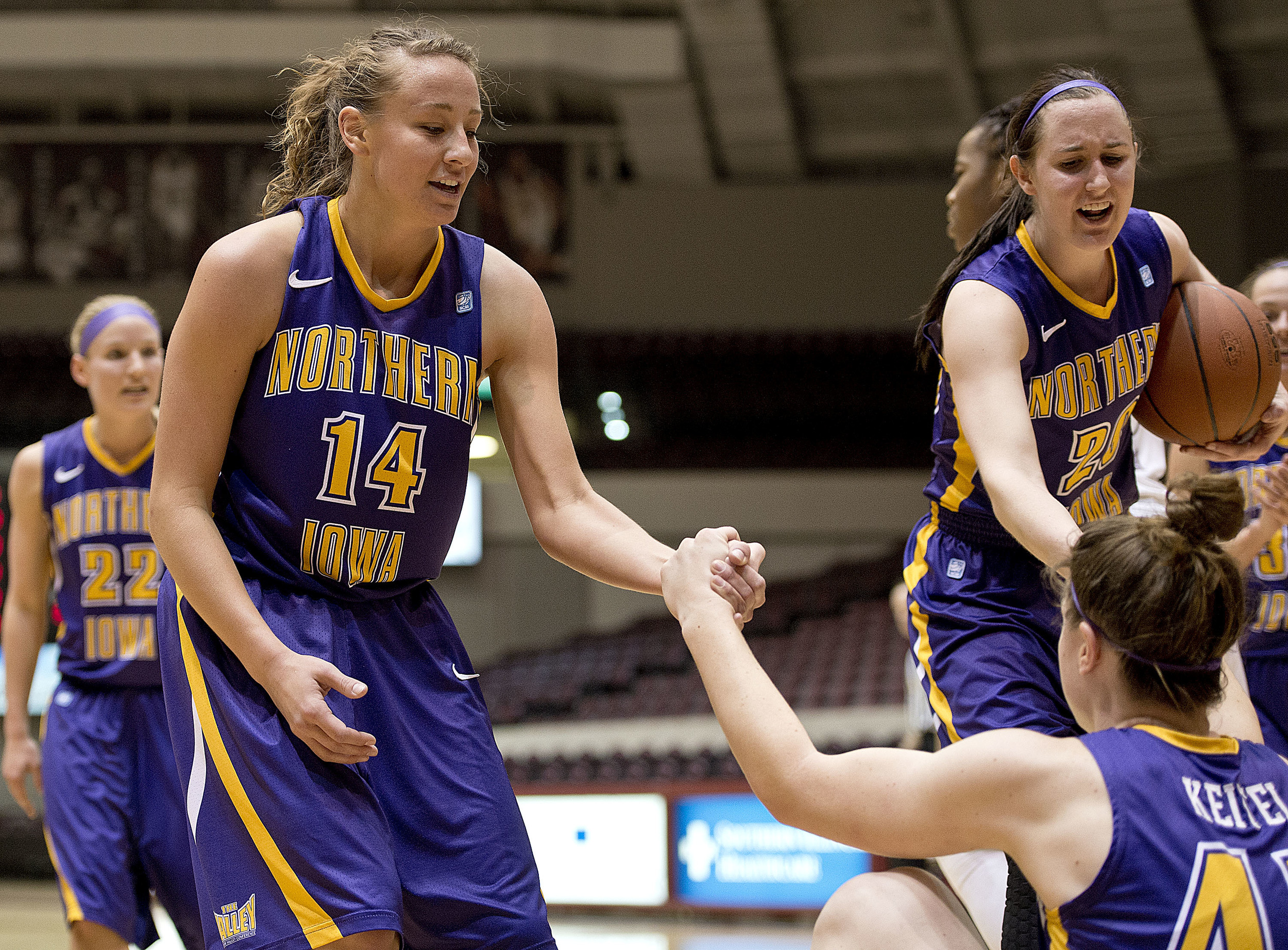 Northern Iowa's Stephanie Davidson, left, and Hannah Schonhardt, right, help Jen Keitel get back up to her feet after taking a charge.