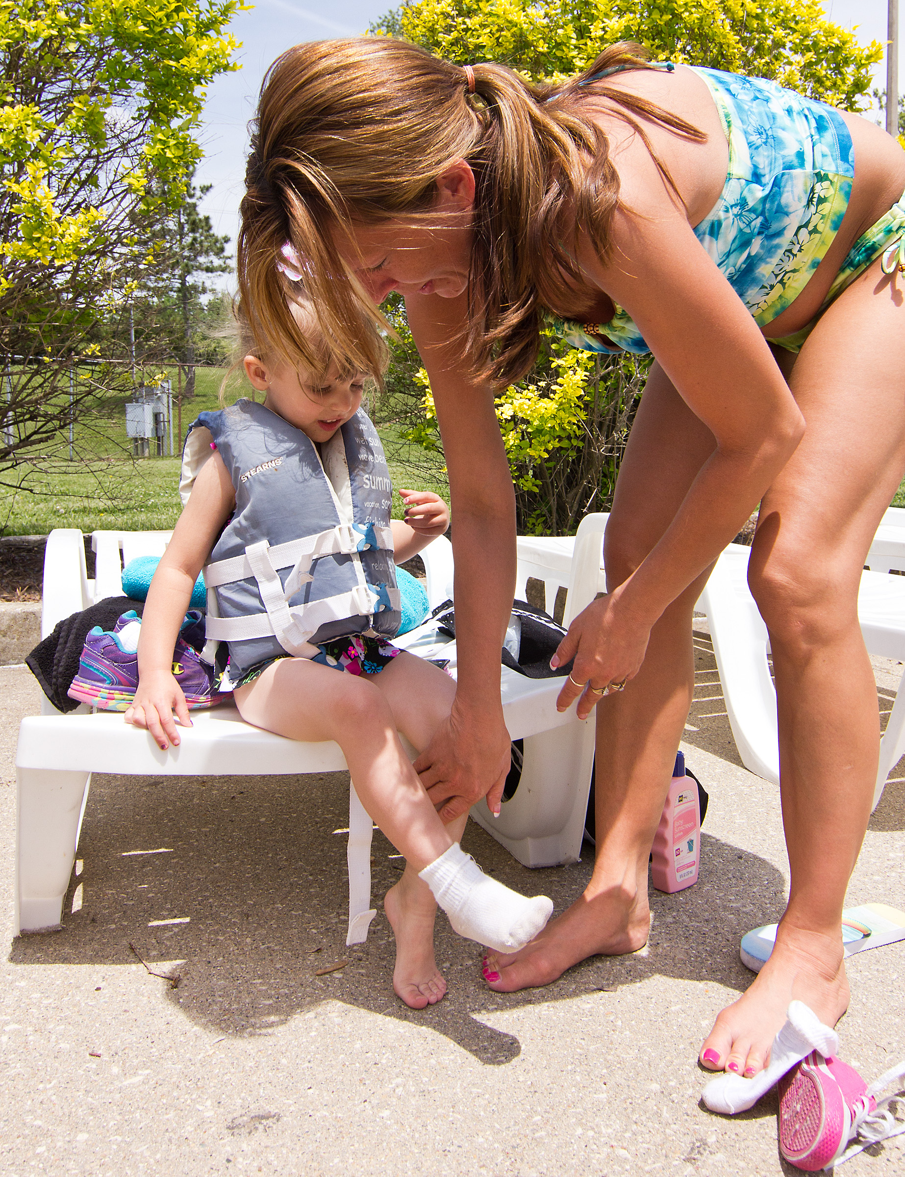 Jill Bundy, of Decatur, Ill., helps her daughter Miracle Schafer, 3, take off her socks before swimming on May 24 at Fairview Pool.