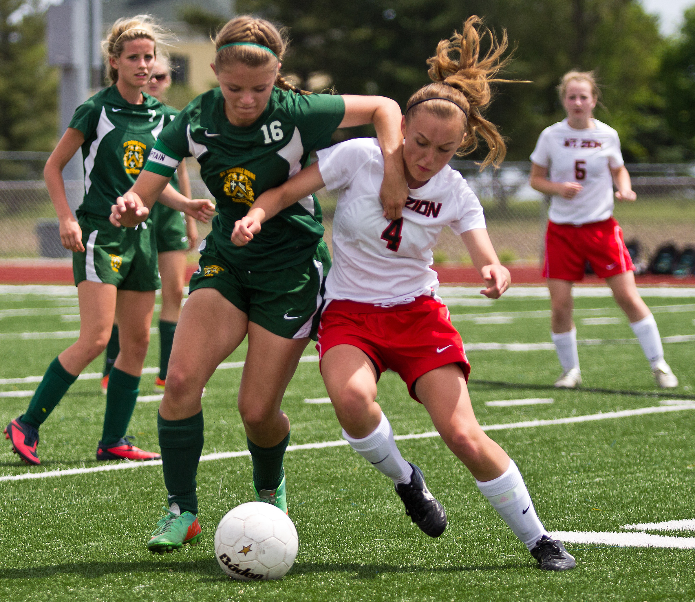 Champaign Saint Thomas More's Michaela Ward, left, and Mount Zion's Morgan Engmann fight for possession during the sectional championship game on May 24 at Walter Boyd Field in Maroa, Ill. The Braves lost to the Sabers 3-2 as Champaign Saint Thomas More claimed their first sectional title in program history.