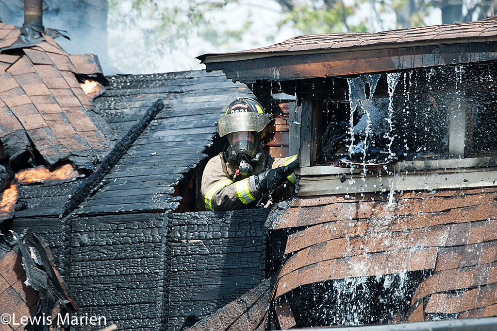 Carbondale Fire Department firefighter Ryan Hall works to put out the remains of a house fire at 208 W. Hospital Drive in Carbondale.