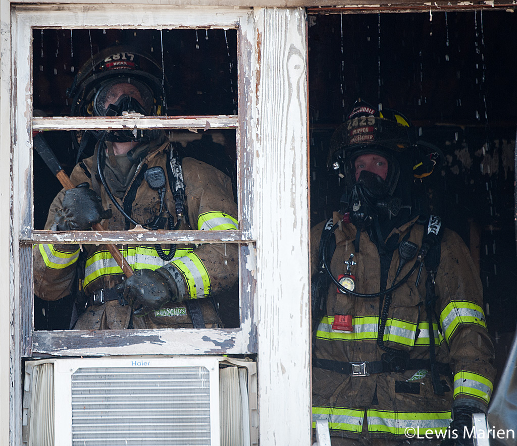Carbondale Fire Department firefighters ChadHicks (left) and Jay Crippen (right) work to put out the remains of a house fire at 208 W. Hospital Drive in Carbondale.